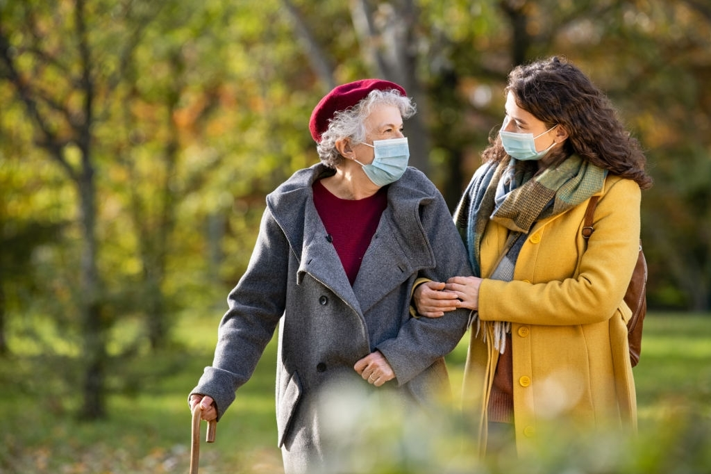 a young woman and an elderly woman taking a walk and both wearing masks