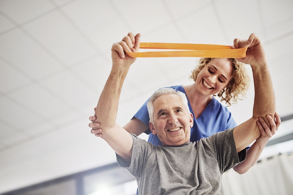 a female medical professional helping an elderly man exercise