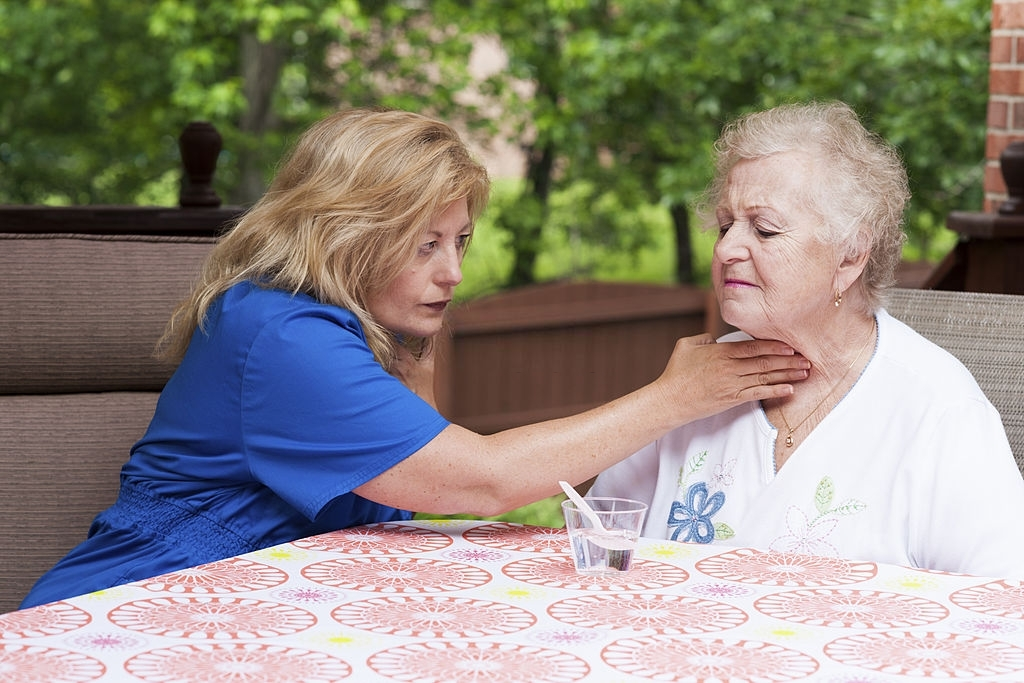 a woman wearing blue checking how the elderly woman swallows