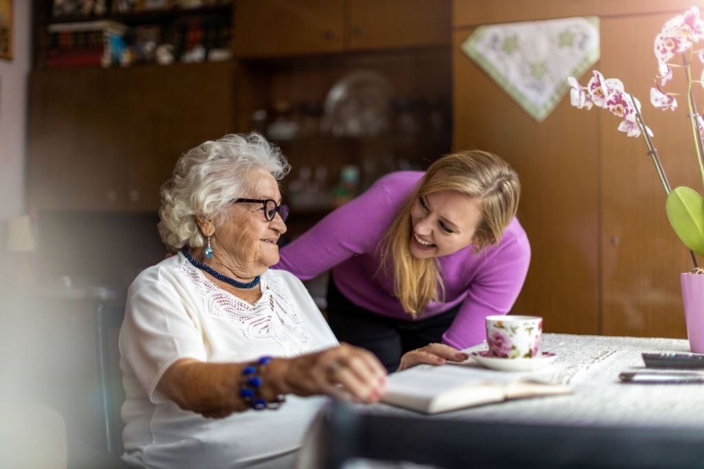 a young woman checking in on an elderly woman who was reading a book