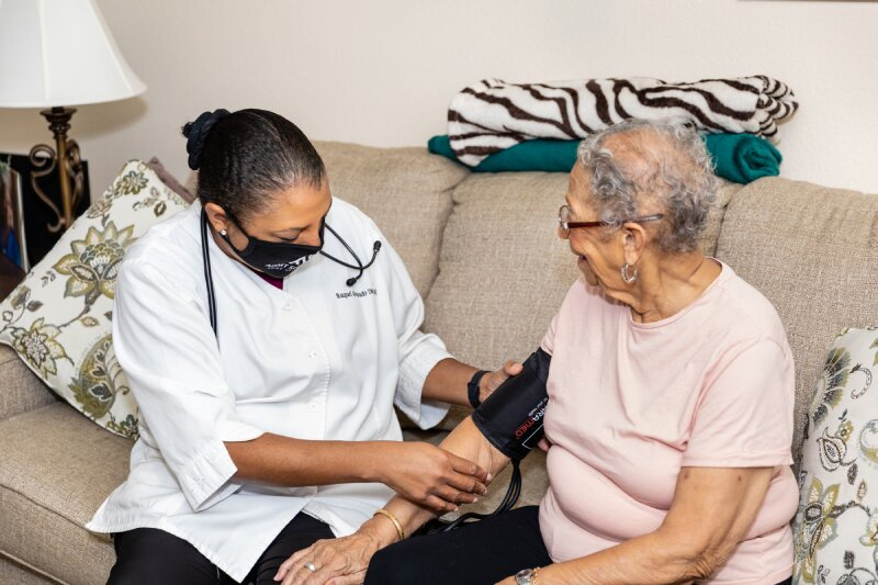 a female medical professional checking the blood pressure of an elderly woman