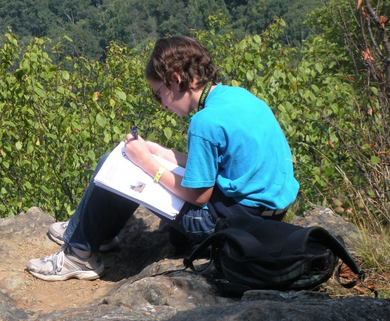 Young adult sitting on a rock sketching the scenery around them.