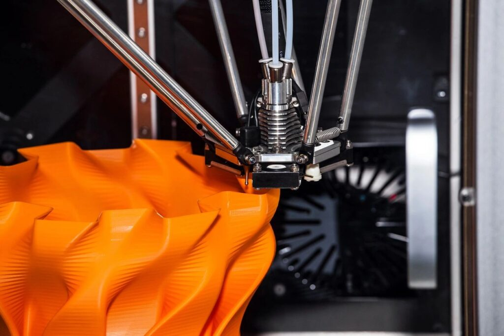 3D Printer fabricating an object out of orange plastic