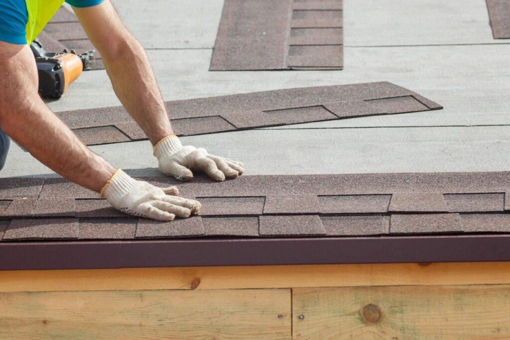 Hands repairing hail damage on a roof