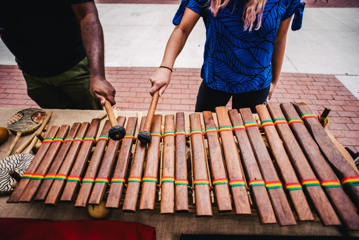 two hands, one black and one white, from two different people, playing a large xylophone together