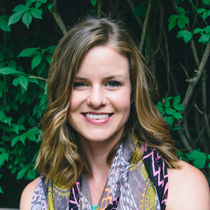 headshot of blog author sunny widman standing in front of green foliage - she has on a multicolored scarf lightly colored skin and long sandy brown hair