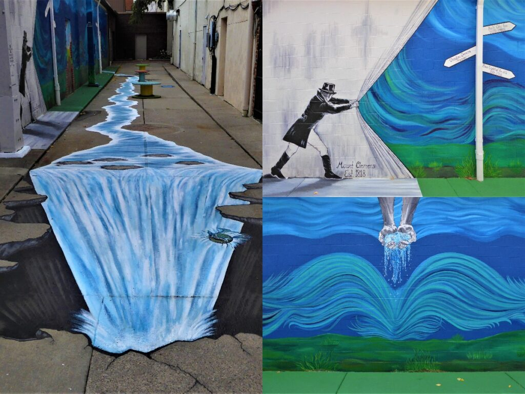 A photo of a mural about water that pours off onto the street and is painted onto the sidewalk and then turns into a waterfall.