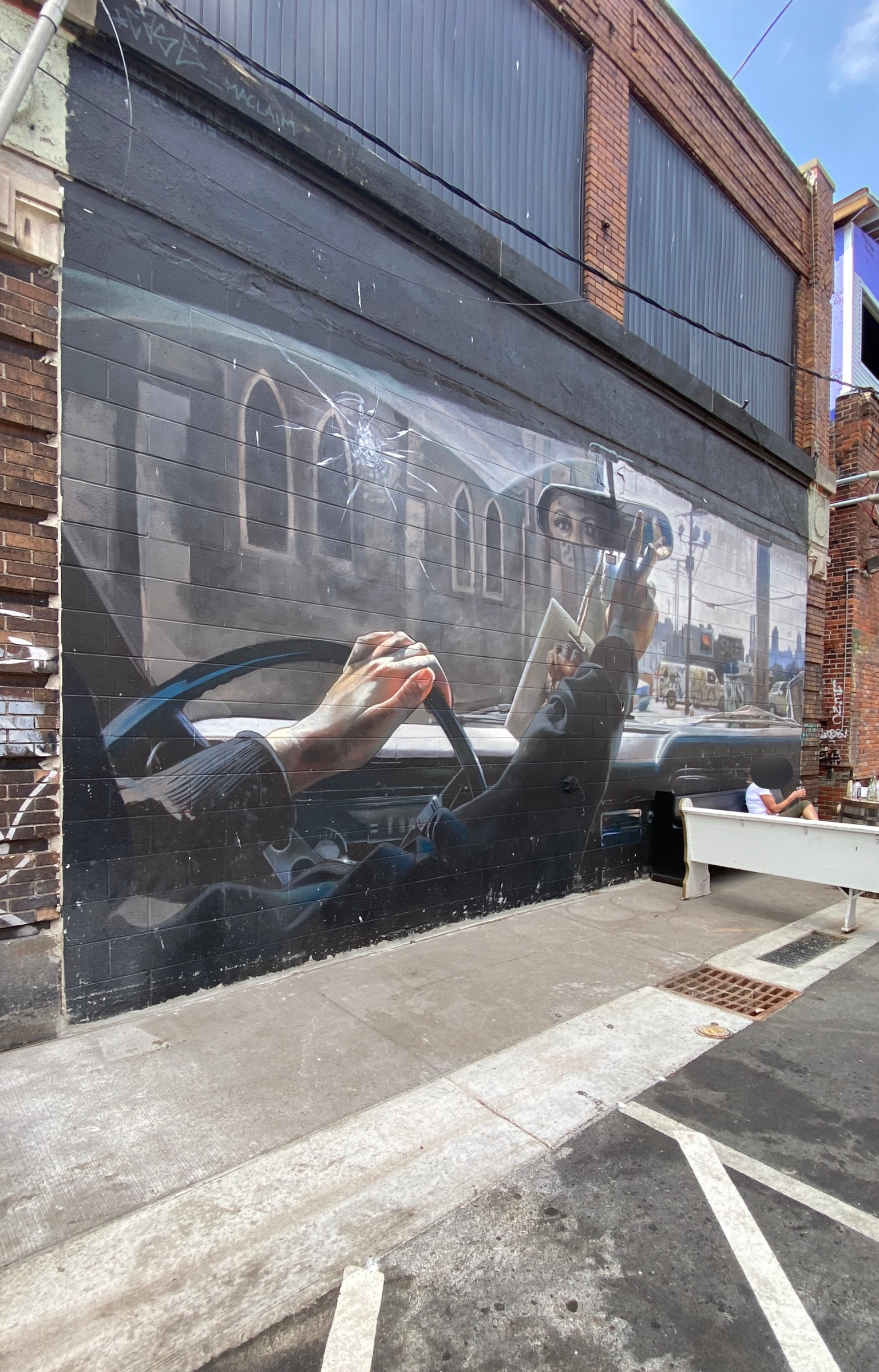 A photo of a mural of a woman behind a steering wheel of a car looking in the rearview mirror, the perspective is from the backseat of the car so all you see is her eyes through the rearview mirror.