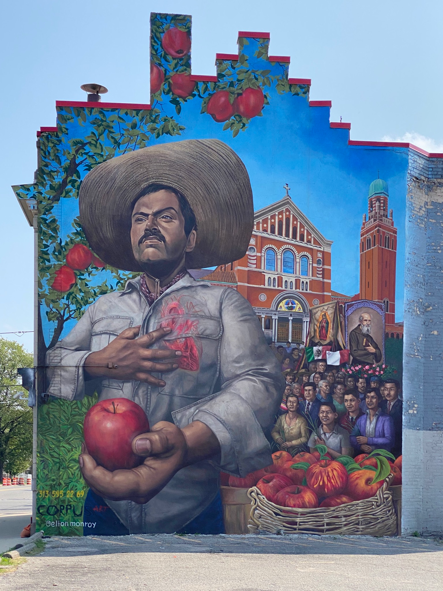 Photo of a mural of a Latinx man holding an apple, holding his hand to his heart, behind him there are portraits of community members and a church in Southwest Detroit