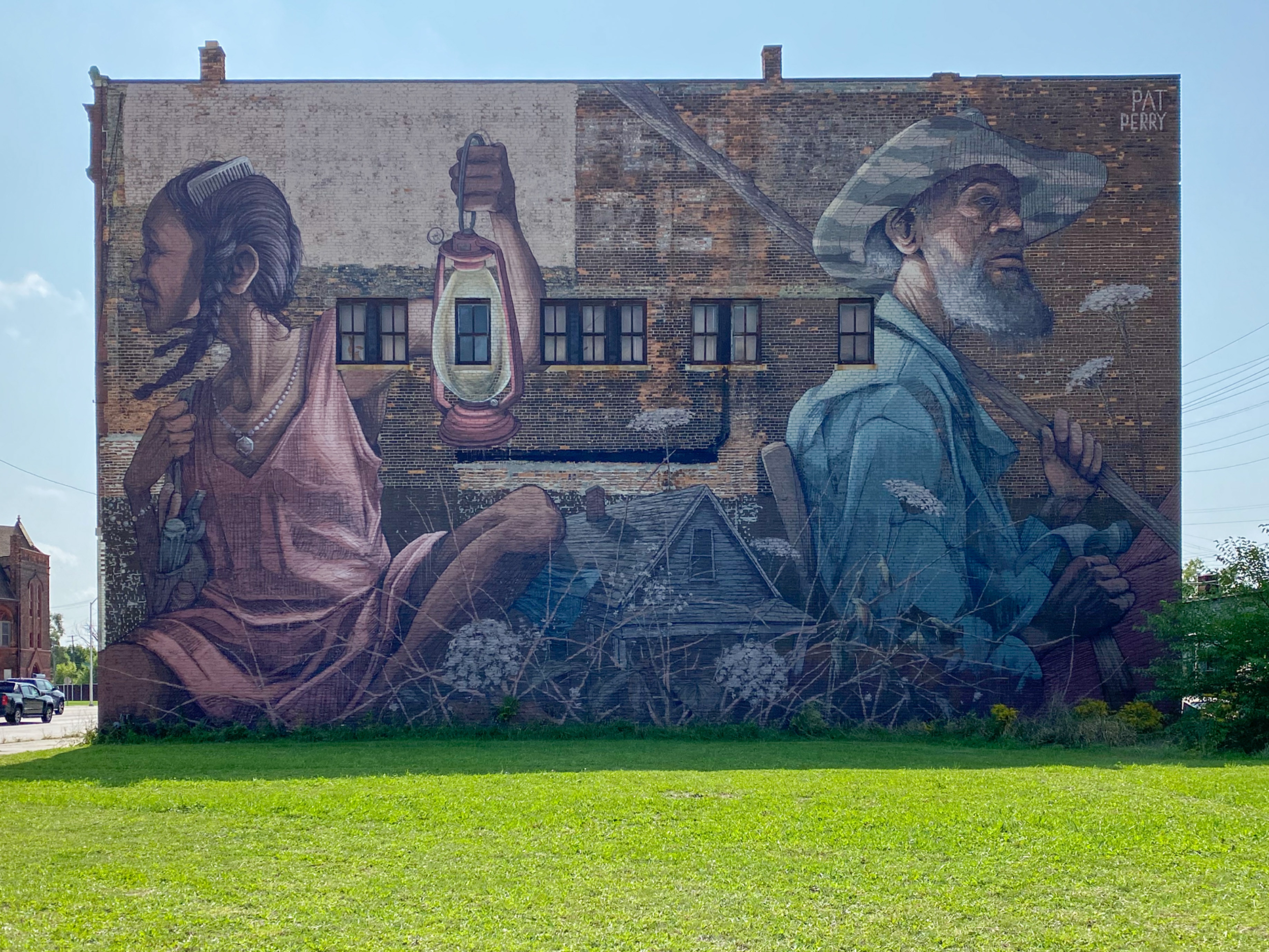 Photo mural on a wall with a young woman holding a lantern and an older man holding a shovel