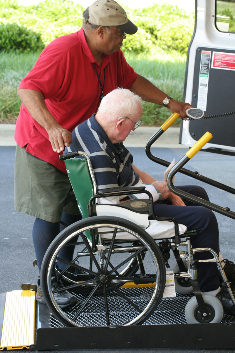 Assistance with transportation, man in wheelchair onto van lift