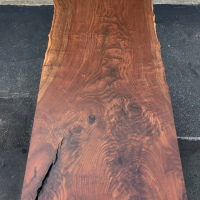 Single plank Claro Walnut dining table with mostly trimmed edge leaving small glimpse of the original live edge