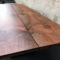 Book matched Walnut dining table with center pencil gap and trimmed edge
