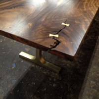 Custom bronze butterflies on single plank, trimmed edge Acacia dining table with T-base