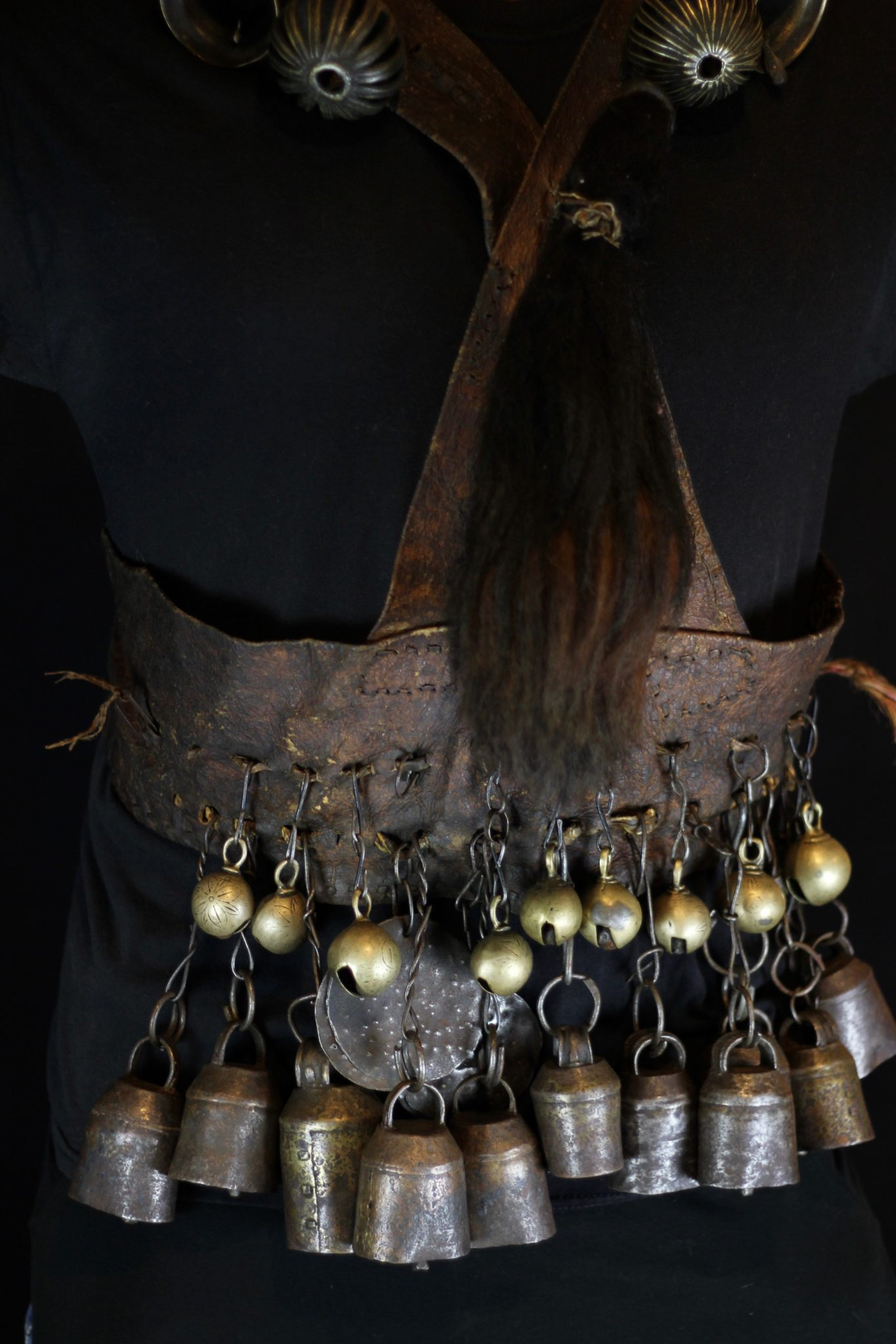 """Shaman Ritual Apron Belt, Nepal, Early 20th c., (some bells up to 150 years old), An essential part of Nepalese shaman costumes, this heavy apron belt is made of hide leather, iron chains, and hand crafted cylindrical bells and bangles, brass conical and crotal bells. The yak tail, and other amulets which are attached, are powerful spiritual tools. They are worn duringrituals and ceremonies to protect shaman and villagers and the area from witches and other evil beings. (it is a waist belt with hanging bells and over the shoulder cross straps), 44"""" x 33"""" x 3"""", $3200."""