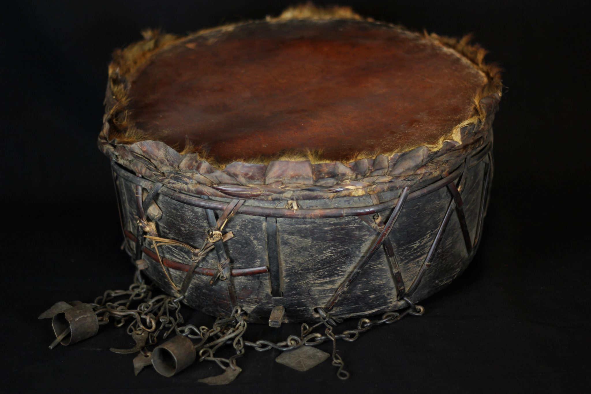 """Sacred Ritual Drum, Nepal, Mid to late 19th c., Skin stretched over wood, iron, shaman bells and amulets, To facilitate entering and maintaining a trance state necessary for the shaman to perform rituals 17 ½"""" x 8"""" x 8"""" (plus 7"""" bell chains), $1400."""