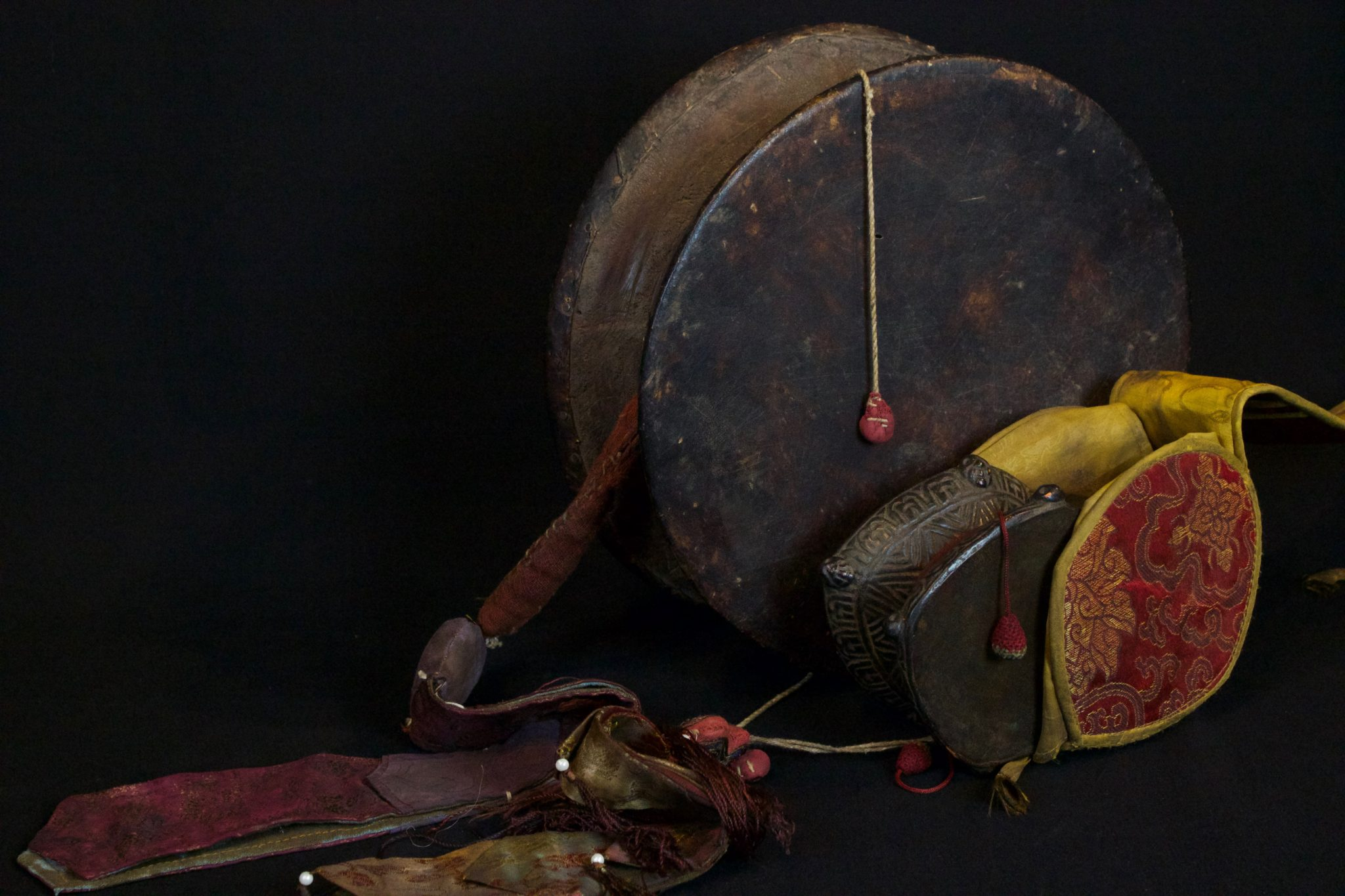 """Damaru with Chopin (2 sided drum with sash), late 19th and early 20th c, wood, hide, fabric This power drum, associated with Shiva, is used for tantric rituals and is played with a twisting motion so the two beaters - attached by cords, hit the drum heads simultaneously. It produces a spiritual sound by which the universe was created and is regulated. The Chopin is typically embroidered with the colors of tantric elements and waves as the drum is played. large - 32"""" x 11"""" x 4 """", $700.; small with case"""