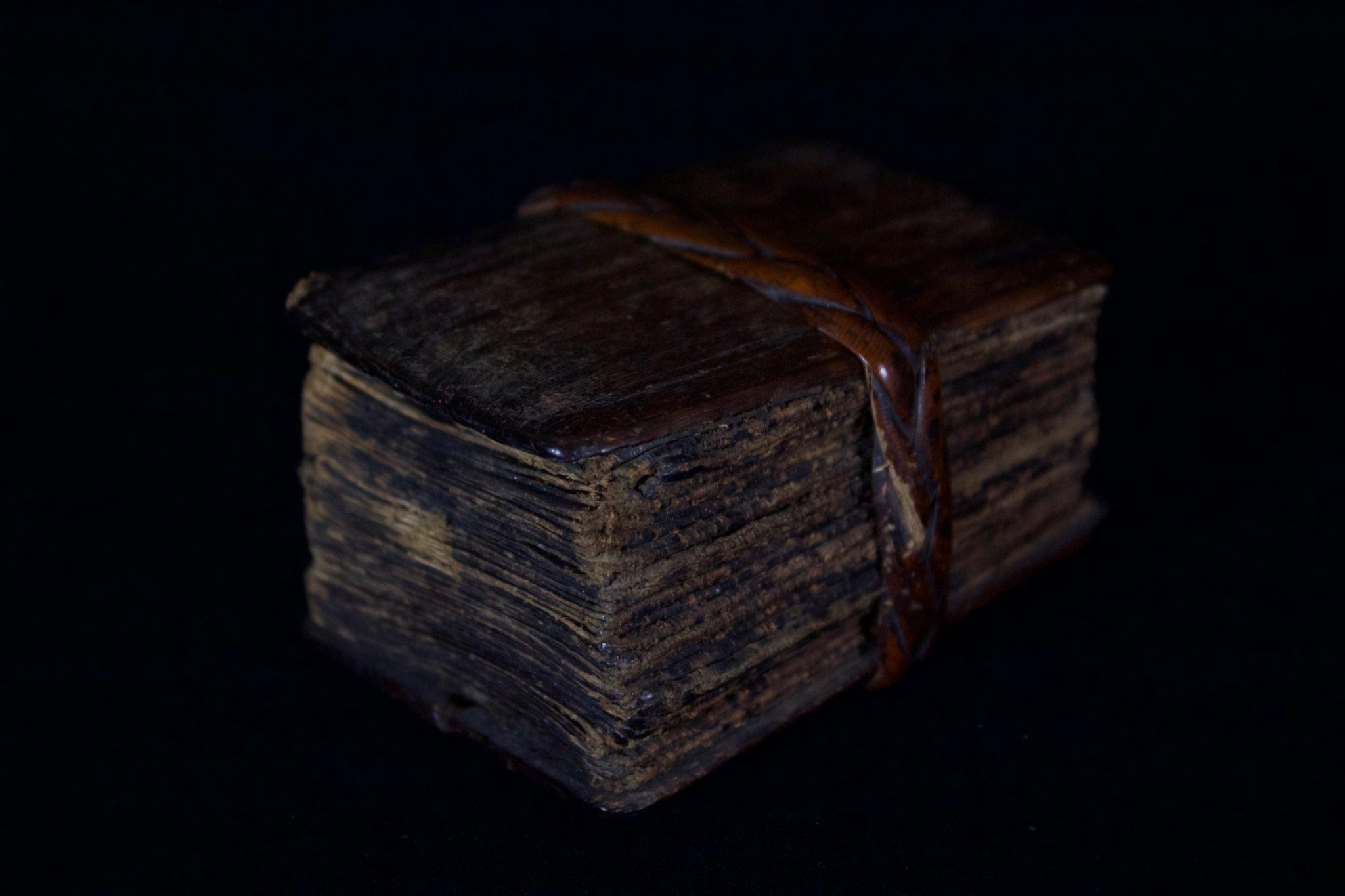 """'Pustaha' or Shaman Medicine/Magic Book, Indonesia, Sumatra, Batak tribe, Wood cover, bark pages and braided rattan band. Late 19th or early 20th c, The book unfolds like an accordion. It contains the shaman's magic formulas (tabas), oracles, recipes for medicines and instructions for performing rituals and for producing magic cures. It contains three main divisions of knowledge: the art of preserving life; the art of destroying life and the art of fortune telling. 1 ¾"""" x 2 ¼"""" x 3"""", $1200."""