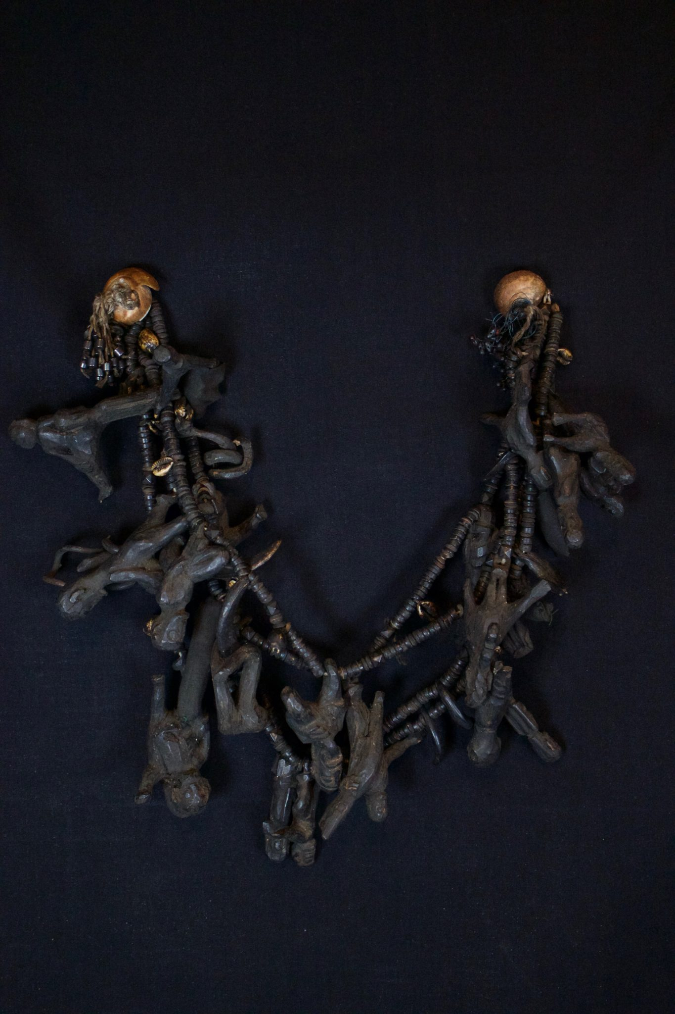 """Shaman Healing Amulet, Necklace, Borneo, Indonesia, Dayak tribe, Mid 19th to early 20th c, Root wood pigmented with soot, shell, animal teeth, cloth pouches, glass beads, disk beads, patinated with age and use. Used for healing rituals. The amulets correspond to various illnesses and conditions. 26"""" x 8"""" x 2 ½"""", $2400."""