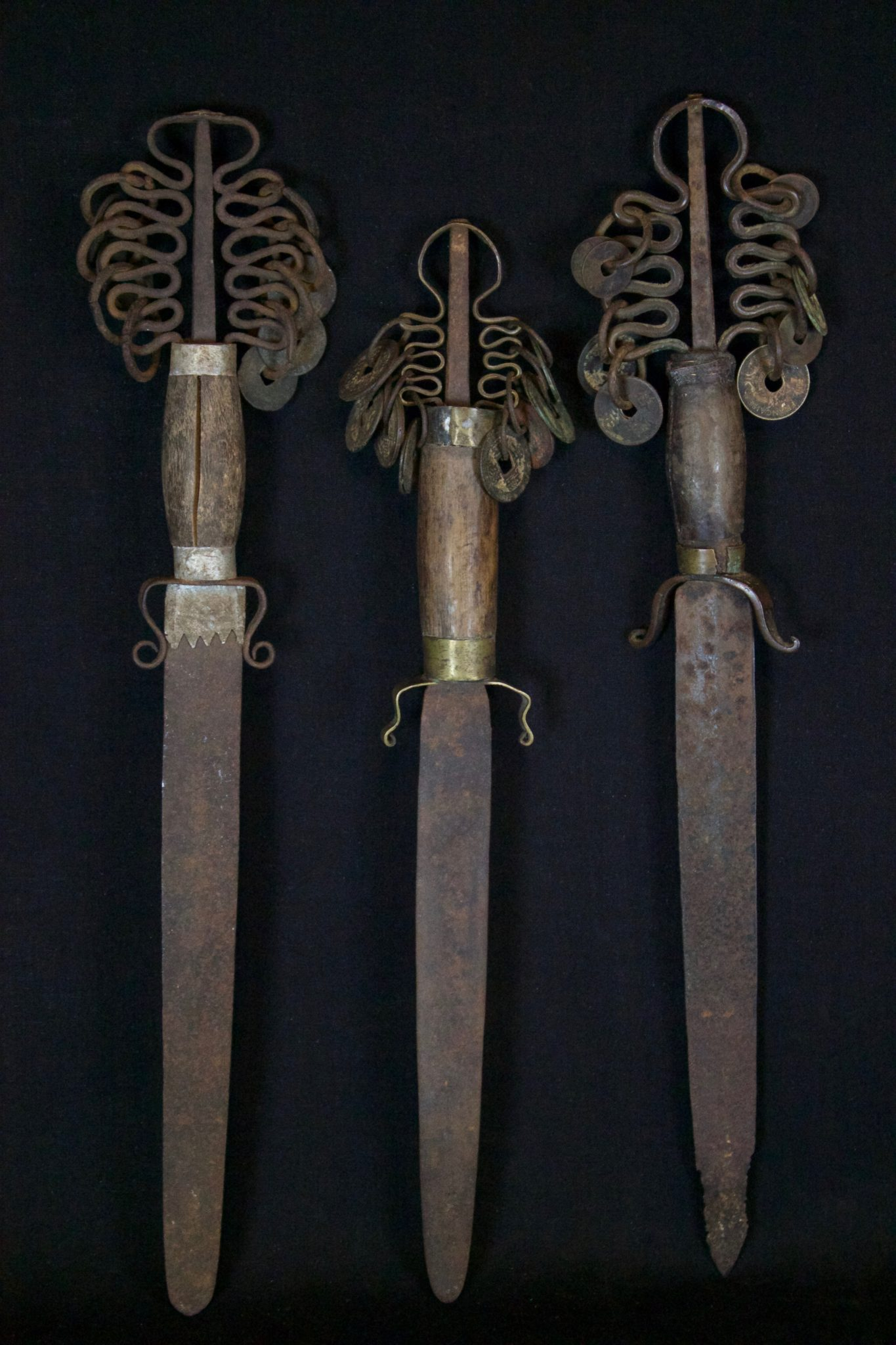 """Ritual Sword, Tuyen Quang province, Vietnam, Yao people, Early 20th c, Iron blade, aluminum bands, wood handle, metal coins, darkened patina from use and age An essential item for any Yao shaman ritual. Used to summon gods and goddesses and to punish disobedient spirits. Harmless to mortals but a formidable weapon when shaken against evil spirits. This is a male sword - top detail differs on female swords. $295. each, Dimensions left to right, (left - 15 ¼"""" x 3 ¼"""" x 1""""); (middle - 15 ¼"""" x 3 ¼"""" x 1""""); (right -13 ¾"""" x 3"""" x 1"""")"""