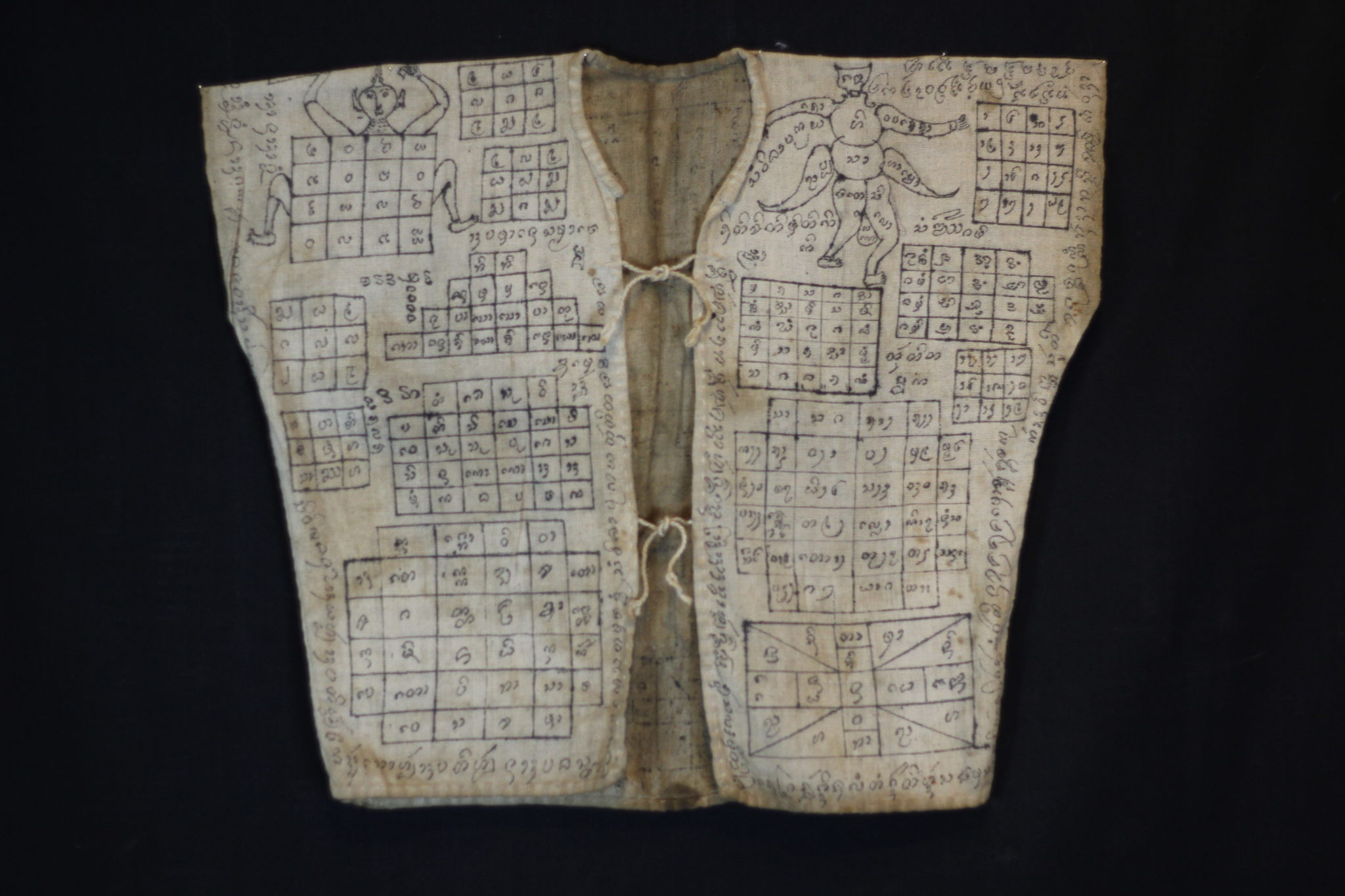 """Amulet Yantra Vest Nong Pho, Thailand Vietnamese shaman Mid to late 19th c. Cotton, pigment Handmade and drawn by the shaman It is endowed with prayers, signs, numbers and a depiction of the great guru monk Luang Phor Doem. The sacred cloth is an undergarment worn as a talisman with great protective power against physical harm, like bullets, spears, knives, wild animals and evil spirits. 19"""" x 22"""" $2,900."""