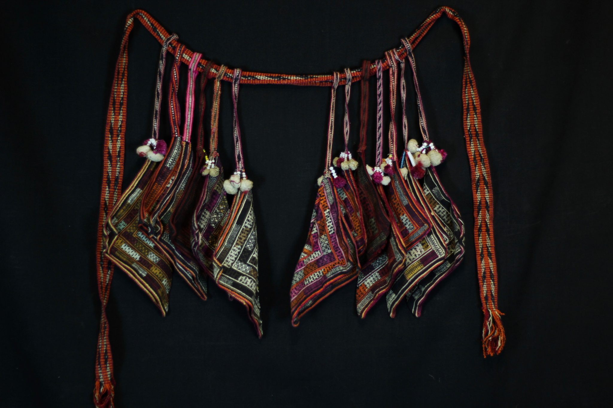 """Shamanic Belt with full set of 12 Handkerchiefs, Da Bac district, Hoa Binh province, Vietnam, Tight Trouser Dao people, Early to mid 20th c. Cotton, hand embroidered with silk. Worn by shaman while performing religious rituals. A complete belt would have a minimum of 12 handkerchiefs (embroidered squares). The belt is passed down through generations, revealing its history. If a shaman has two sons or apprentices, he will spit the belt and the new shaman's wife will make the other necessary handkerchiefs. 75"""" x 18"""" x 2 ½"""", $775."""
