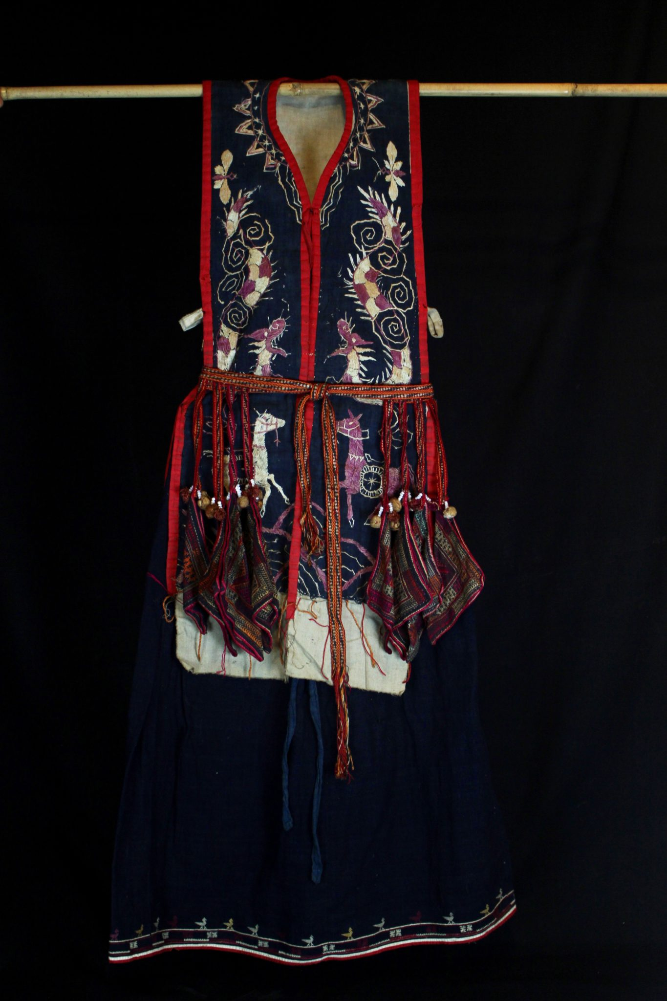 """Shaman's Costume Tunic and Belt, Vietnam, Yao people, Late 19th c, Cotton, indigo, silk embroidery, Worn only by high level shaman. The motif typically includes all the deities of heaven to clothe the shaman in the protection of the universe. Not a vain adornment, it is a reminder of man's place in the hierarchical order. Originally a female costume. Long ago shamans were women and men the providers. Not being encumbered by childbirth and rearing, men replaces women as shamans but retained this part of the sacred costume. *more information available. 47"""" x 27 ½"""" x 3"""", $3100."""