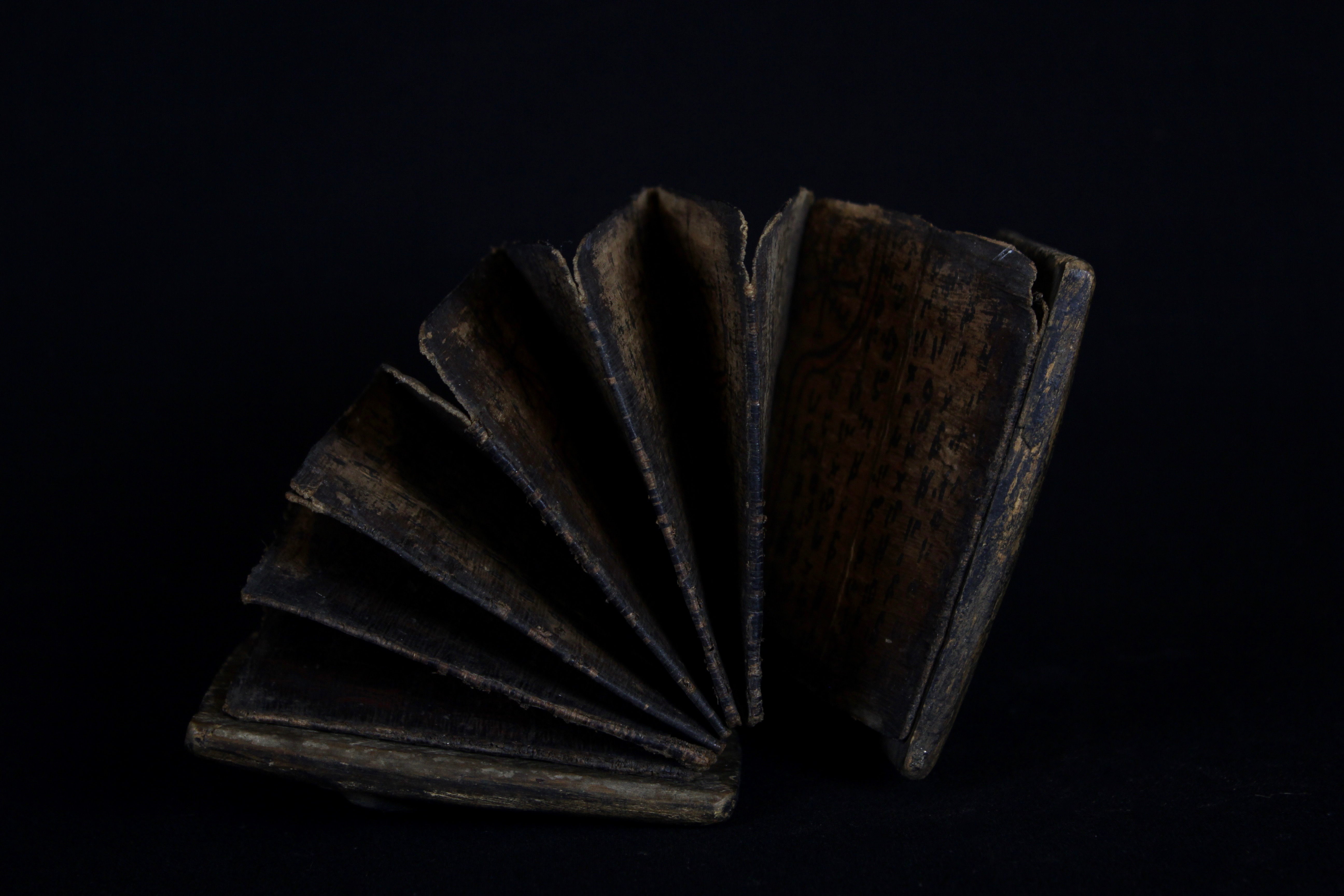 """Inside Detail of 'Pustaha' or Shaman Medicine Book, Indonesia, Sumatra, Batak tribe, Wood cover, bark pages and braided rattan band. Late 19th or early 20th c, The book unfolds like an accordion. It contains the shaman's magic formulas (tabas), oracles, recipes for medicines and instructions for performing rituals and for producing magic cures. It contains three main divisions of knowledge: the art of preserving life; the art of destroying life and the art of fortune telling. 4 ½"""" x 3 ½"""" x 2"""", $2200."""