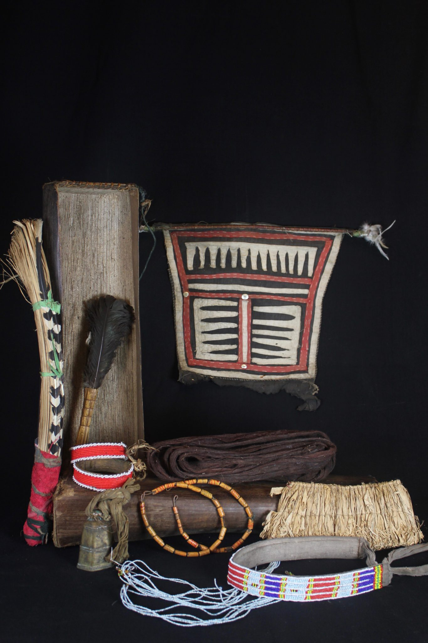 """Shaman Kit Box Contents, Mentawai Islands, Sumatra, Indonesia, Mentawai tribe Early to mid 20th c, Case: sago palm leaf box, braided rattan, Raffia wand handle and headband, feathers, European glass trade beads, cotton trade cloth, wood, bronze bell. Contents: costume (loincloth, jewelry, head gear) and wands. All items have a specific purpose - example: the beaded headband acts like antenna attracting spirits the shaman needs to contact. 5 ½"""" x 7 ½"""" x 30 ½"""" $3600."""