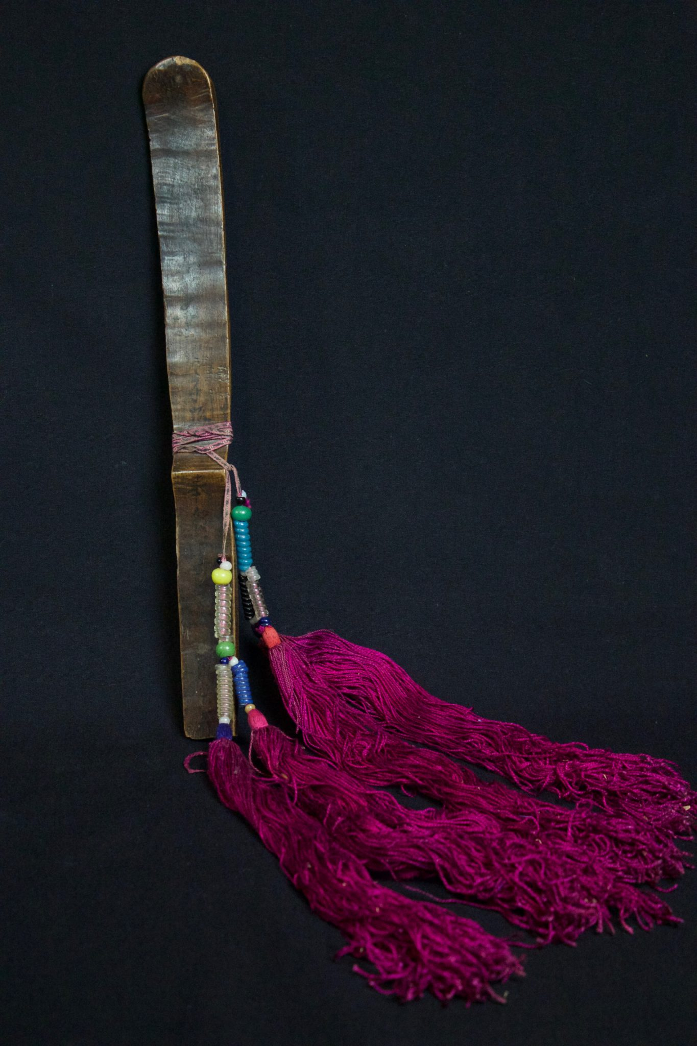 """Shaman's Court Tablet or Wand, Vietnam, Yao people, Mid to late 19th c, Wood, finely woven cotton band with glass beads. Potent tool used similarly to a Himalayan Phurba, to direct evil energy away and to summon and control spirits. Text characters are painted onto all sides. 13 ¼"""" x 16 ½"""" x ¾"""", $650"""