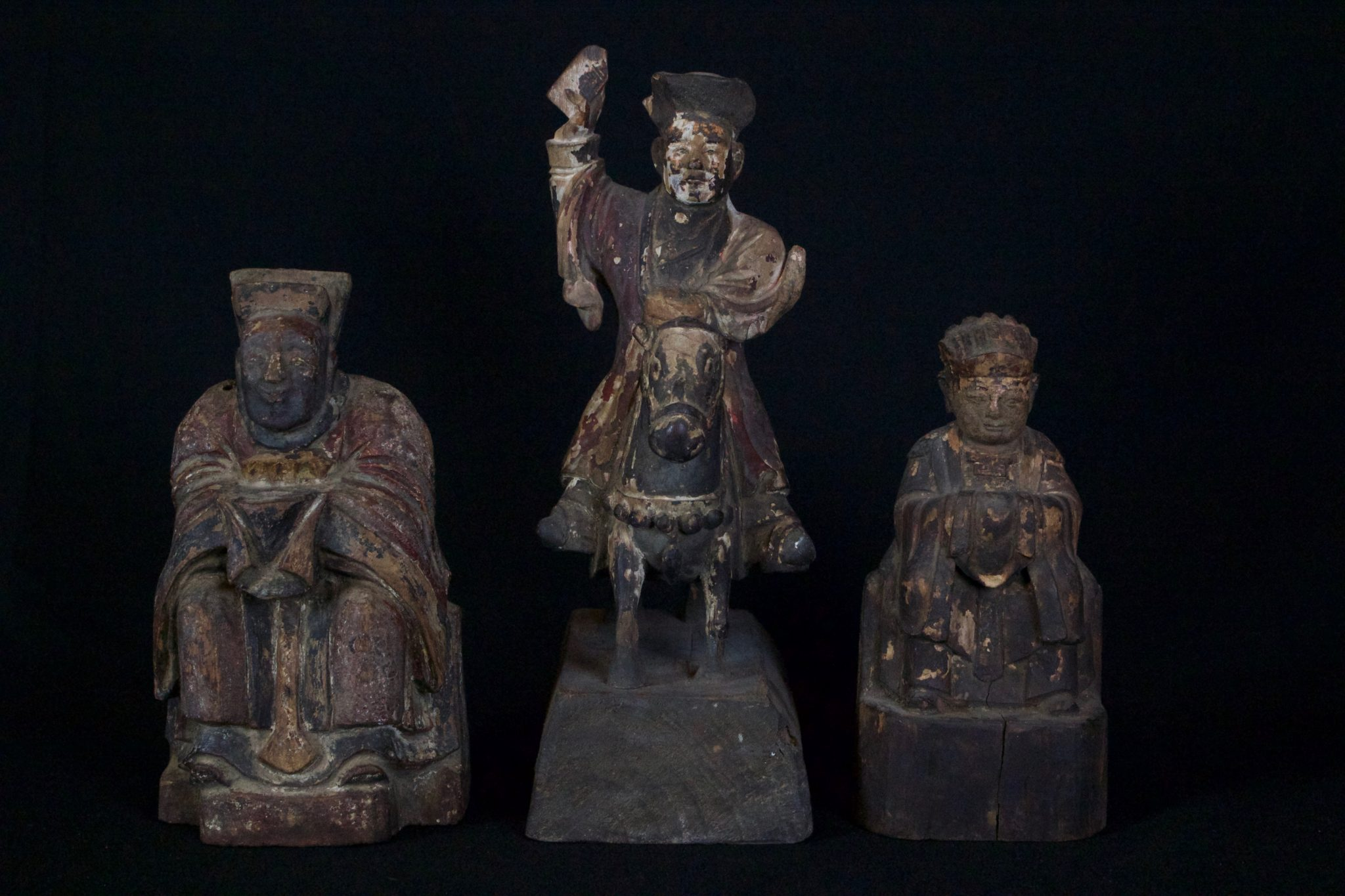 """Zhu Zhong Fan, Shaman Priest Altar Figures, Vietnam, Yao people, Mid to late 19th c, Wood, pigment, Kept in Shaman's home. Part of necessary items to contact spirit world. Every shaman has a set of three called, Zhu Zhong Fan figures. The 3 are: To Sai - ancestor shaman priest figure; Nyut Hung - seated Mandarin or God figure; and Khong Zhao - a protecting officer or messenger to the gods. He is always mounted and brandishing a sword or pennant. They are only sacred when once they are gifted with a soul. A ceremony is performed calling for the deity or ancestor to enter the figure. A piece of silver and some threads are placed in a secret hole in the back and sealed up. This is where the soul resides. When the figure is given away or sold the silver is removed rendering the figure inert and no longer sacred. (left - 'Nyut Hung' figure, 8"""" x 4 ¼"""" x 2 ½"""", $650); (middle - 'Khong Zhao' figure, 11"""" x 4"""" x 6 ¾"""", $900.); (right - 'To Sai' figure,7"""" x 3 ¼"""" x 2 ½"""", $650)"""