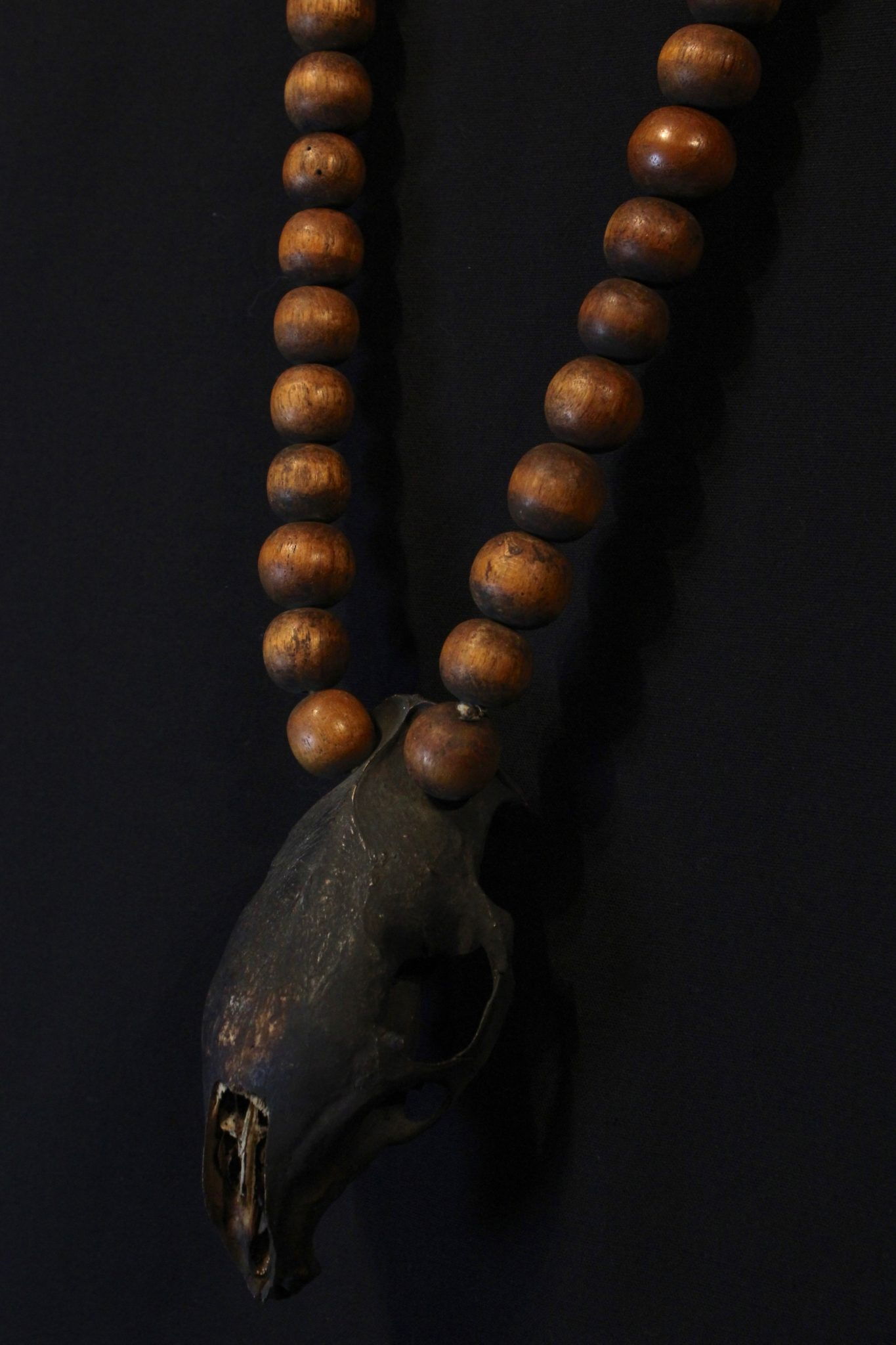 """Skull Necklace Kalimantan, Borneo, Indonesia, Dayak tribe, Early 20th c, Wooden Beads, Rodent Skull, darkened with soot. Worn for healing and protection rituals 17 ½"""" x 2 ¾"""" x 1 ¾"""", $450."""