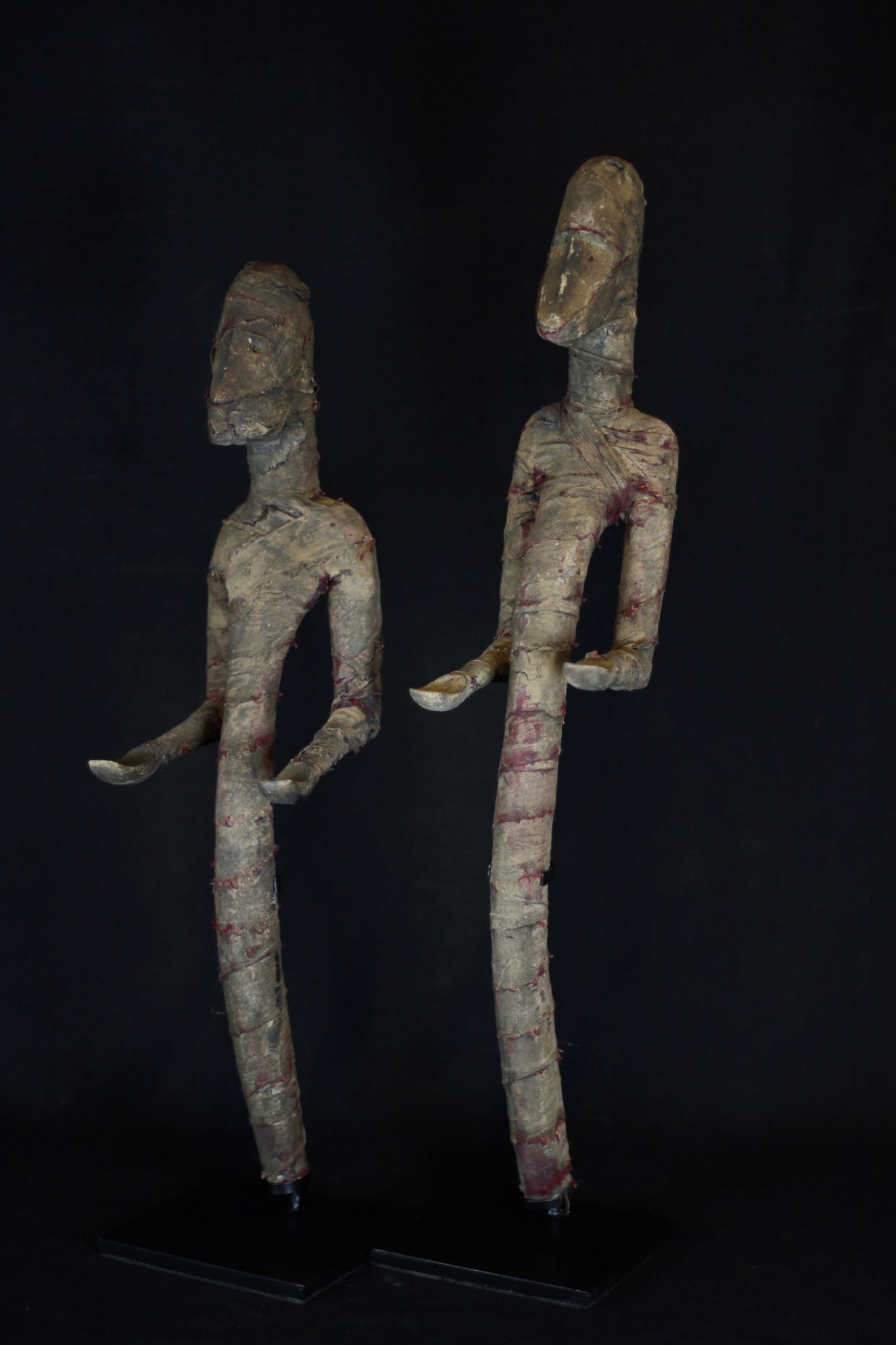 """Shaman Figure (rare), Atauro Island, Lesser Sunda Islands, Indonesia Early 20th c. Wood, cloth. Used to protect people from harmful spirits during rituals. Faded and patinated with use and age, original red color of cloth still visible. Dimensions: (left - 22 ½"""" 5 ½' x 7 ½"""", $1200.); (right - 25 ¼' x 4 ¼"""" x 6 ½"""", $1200.)"""