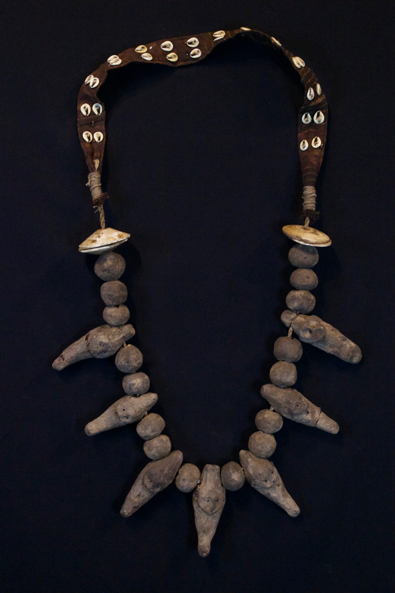 """Shaman Amulet Necklace, Timor Island, Lesser Sunda Islands, Indonesia, Early 20th c, Ceramic stone figures and beads, shell, cotton. Worn by the shaman for healing ceremonies. 21"""" x 11"""" x 1 ¾"""" $650."""