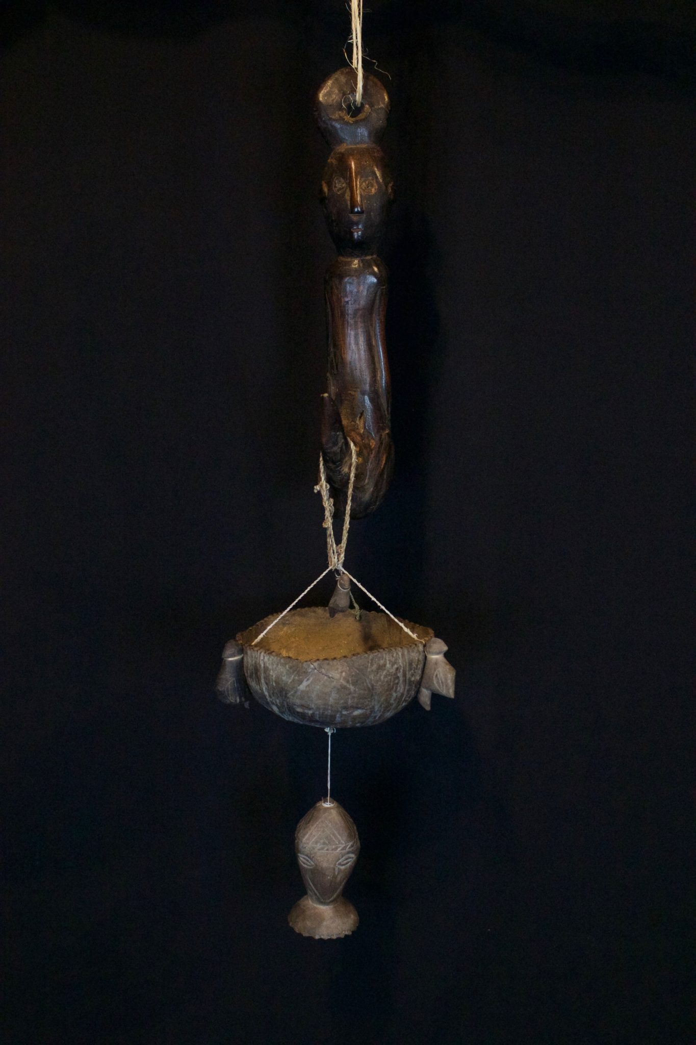 """Hanging Effigy and Herb Bowl - set, East Sumba Island, Indonesia, Soru village, Early 20th c, Wood, coconut, fiber string. The effigy hanger gives great healing power to the herbs placed in the coconut bowl suspended below it. The bowl has three bird figure and three carved faces with an amulet head hanging below it. 30"""" x 6"""" x 6"""", $1200."""