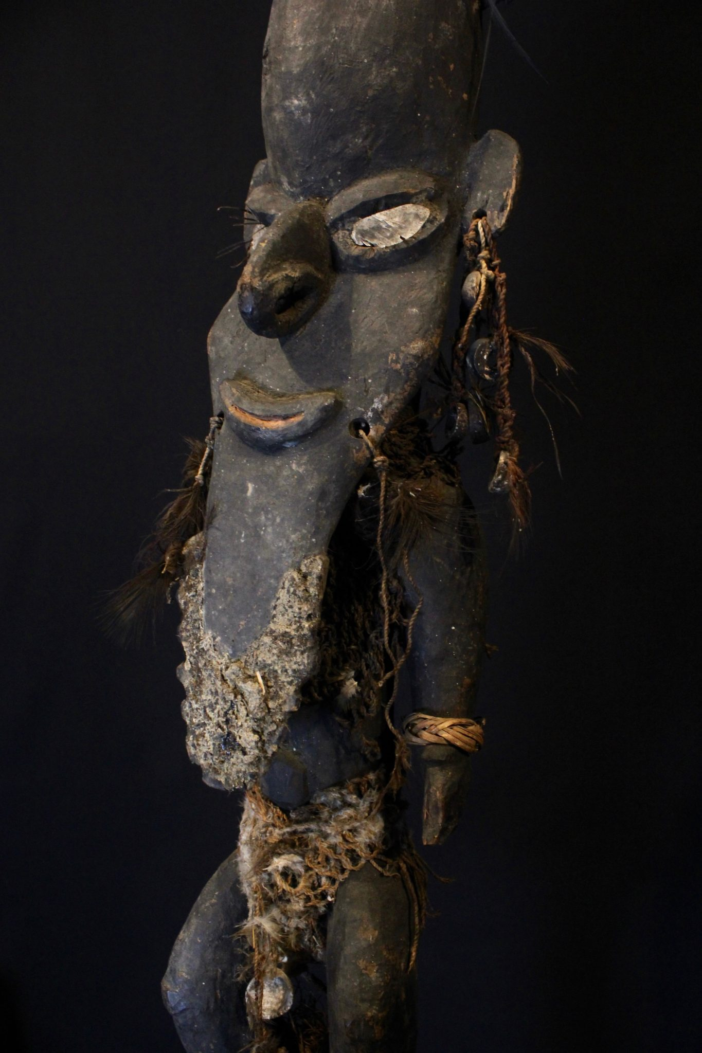 """Sacred Flute with Wusear Effigy Stopper, East Sepik Province, Papua New Guinea, Indonesia, Biwat people, Early 20th c, Flute body - Bamboo, raffia. Effigy Figure - Carved in wood, this figure is particularly elaborate - shell eyes, feather eyelashes, woven clothing and shell and feather adornments with tar and string. Played in pairs for the initiation ceremony for boys. The flute had the power to be voices of the spirits. The anthropomorphic figures or Wusear are specific to these flutes and were inserted into the top when not in use to prevent evil spirits from entering the sacred instruments. They were kept in the homes of the shaman and it was taboo for women and children to see them. 55"""" x 9 ½"""" x 8"""", $9500."""
