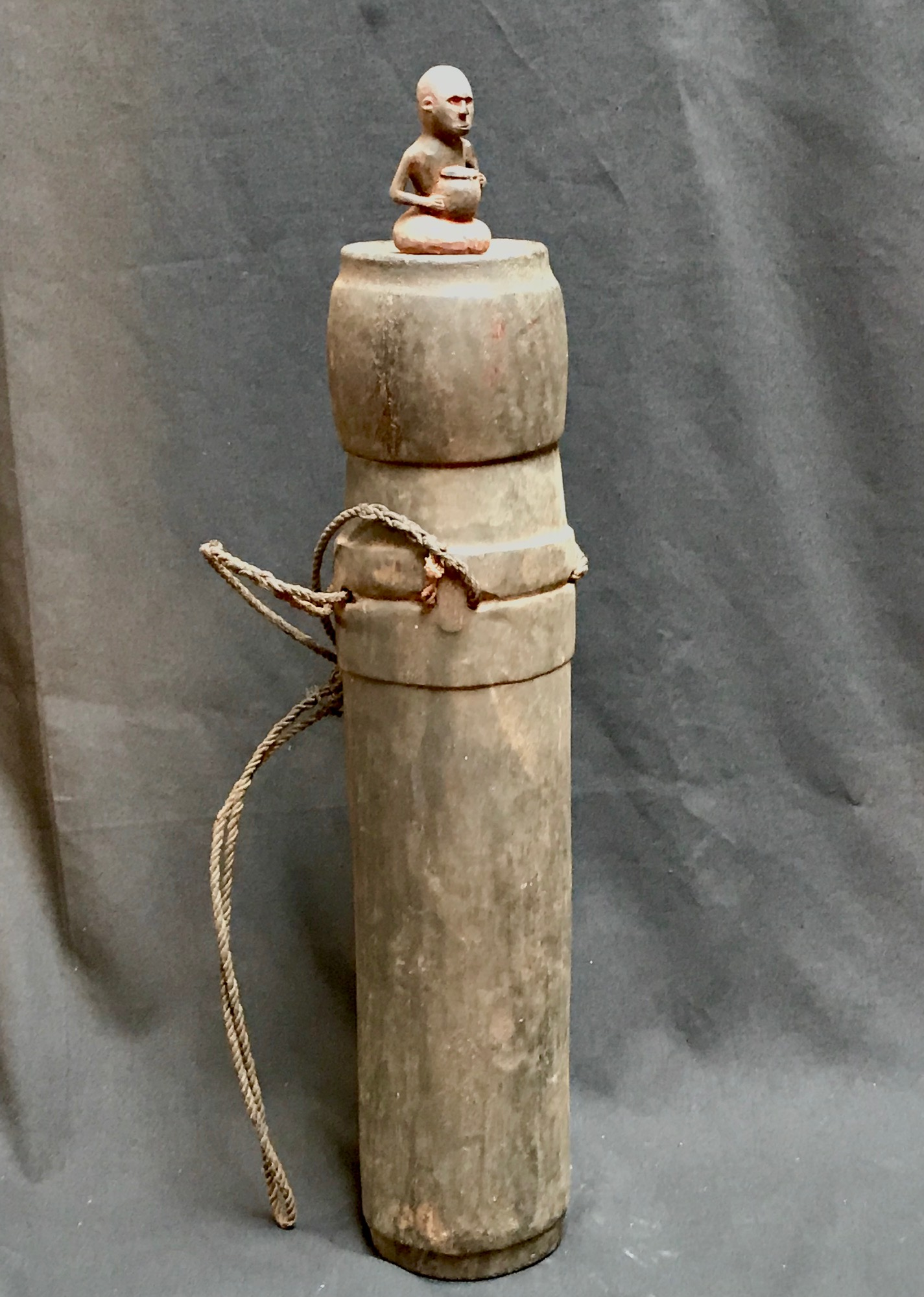 """Shaman's Medicine Jar/Container for healing herbs and substances, with carved seated figure holding a ceramic or wooden vessel. Sumba Indonesia, early 20th c., bamboo, wood, twine, pigment, 23"""" x 7"""""""