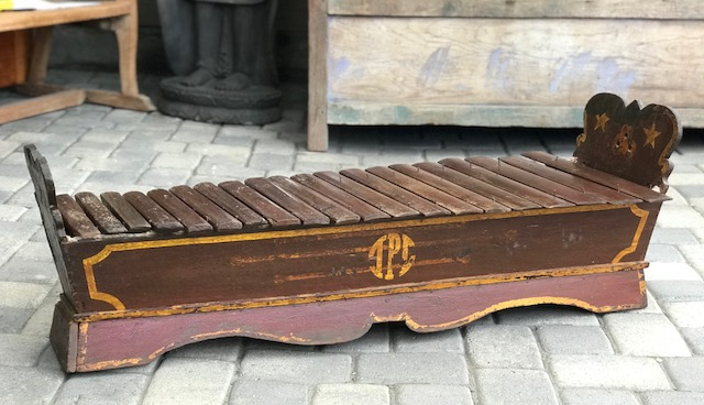 """Traditional wooden xylophone or Gambang Kayu, Java, Indonesia, Early 20th c, wooden resonating box (grobog), 20 hardwood keys (wilah), played with 2 padded wooden mallets and the larger keys on the player's left. The 2 risers on each end are similarly detailed with a star motif and 3 small circular holes and a monogram on the side panel; it is usually played as part of an ensemble called a Gamelan; 16 1/4"""" x 49 1/4"""" x 19""""; $750.; thedavidalancollection.com , solana beach, ca"""