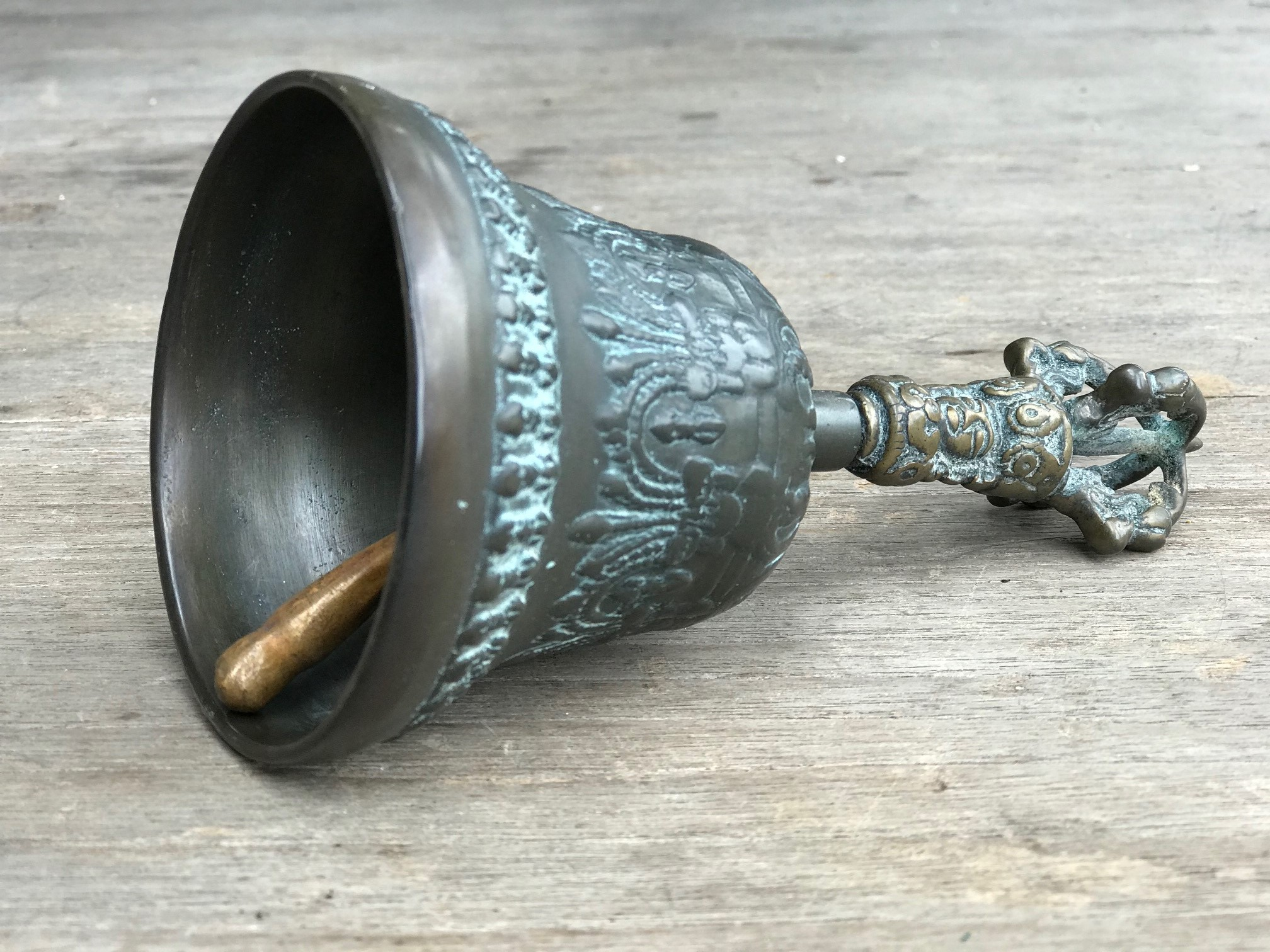 """detail of Musical Instrument, temple clapper bell with face, Nepal, 150 years old, bronze, The Bell, representing the female aspect, stands for wisdom. It is held in the left hand. If the Dorje (crown motif on top) is separate, it is held in the right hand. The are always used in combination in religious ceremonies. Together they represent enlightenment. 6 1/2"""" x 3 1/4"""", $900. thedavidalancollection.com , solana beach, ca"""