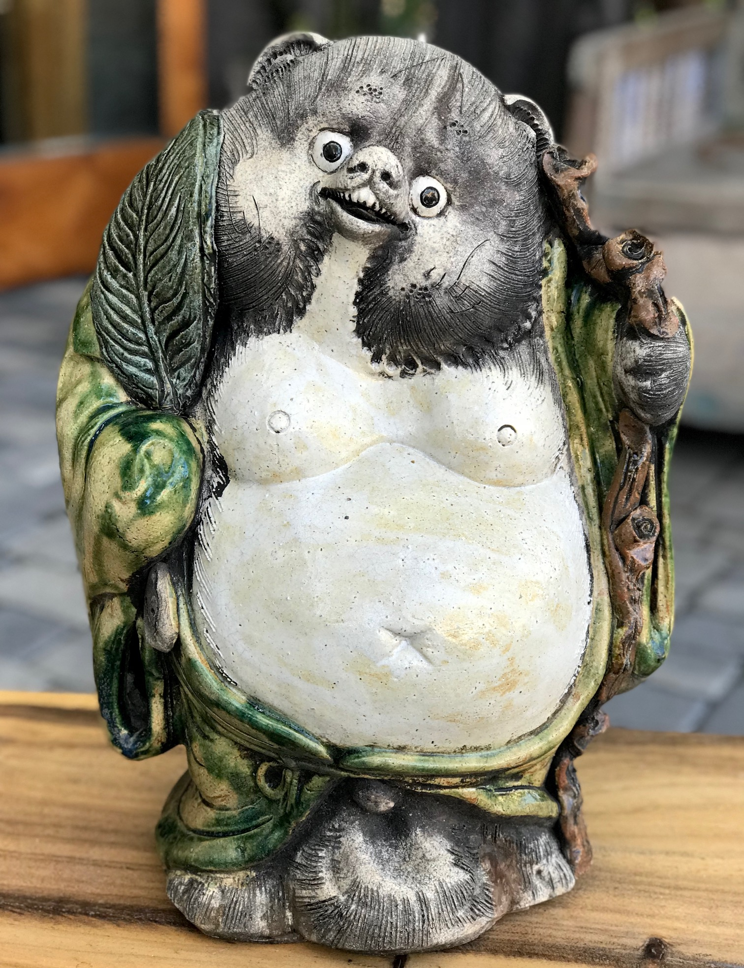 """Shigaraki Tanuki with green robe and feather, Tanuki have a very complex and interesting folkloric history. While largely unheard of in the states, Tanuki have been among the most significant characters in Japan since ancient times. Contemporary Tanuki are primarily a welcoming symbol of prosperity. In the mid 20th century the character was adapted, both visually and symbolically, to suit modern culture and, although they retain much of their prankster persona from the original 16th century creatures, they are much more benign. They have a long list of supernatural powers, most notable shape-shifting. Ancient Tanuki, humorously portrayed in block prints are now mostly found in museums and private collections. Tanuki statues are often found in restaurant or shop windows and outside temples. Famous for getting drunk and not paying their bills, they are usually portrayed wearing a straw hat and carrying a flask of sake and a ledger of promissory notes. Thus they can also serve as cautionary figures against the hazards of overindulging in alcohol. They always have big bellies and humorously large testicles which they use as drums. 18"""" x 12"""" x 13 1/2"""" x 12 1/2"""", $675., thedavidalancollection.com , solana beach, ca"""