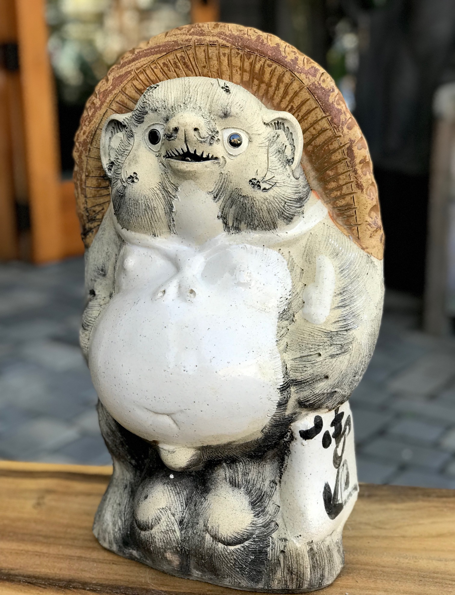 """Shigaraki Tanuki, Tanuki have a very complex and interesting folkloric history. While largely unheard of in the states, Tanuki have been among the most significant characters in Japan since ancient times. Contemporary Tanuki are primarily a welcoming symbol of prosperity. In the mid 20th century the character was adapted, both visually and symbolically, to suit modern culture and, although they retain much of their prankster persona from the original 16th century creatures, they are much more benign. They have a long list of supernatural powers, most notable shape-shifting. Ancient Tanuki, humorously portrayed in block prints are now mostly found in museums and private collections. Tanuki statues are often found in restaurant or shop windows and outside temples. Famous for getting drunk and not paying their bills, they are usually portrayed wearing a straw hat and carrying a flask of sake and a ledger of promissory notes. Thus they can also serve as cautionary figures against the hazards of overindulging in alcohol. They always have big bellies and humorously large testicles which they use as drums. 18 1/2"""" x 11"""" x 11"""", $575., thedavidalancollection.com , solana beach, ca"""