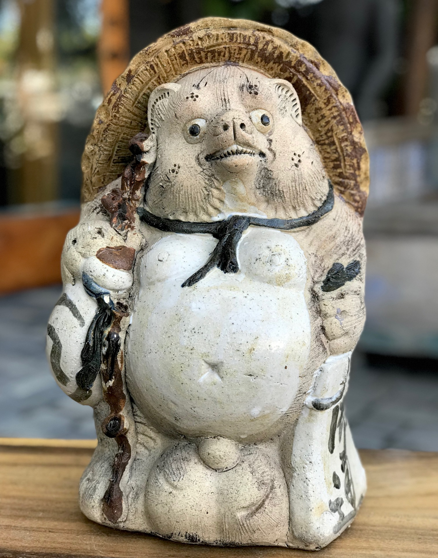 """Shigaraki Tanuki, Tanuki have a very complex and interesting folkloric history. While largely unheard of in the states, Tanuki have been among the most significant characters in Japan since ancient times. Contemporary Tanuki are primarily a welcoming symbol of prosperity. In the mid 20th century the character was adapted, both visually and symbolically, to suit modern culture and, although they retain much of their prankster persona from the original 16th century creatures, they are much more benign. They have a long list of supernatural powers, most notable shape-shifting. Ancient Tanuki, humorously portrayed in block prints are now mostly found in museums and private collections. Tanuki statues are often found in restaurant or shop windows and outside temples. Famous for getting drunk and not paying their bills, they are usually portrayed wearing a straw hat and carrying a flask of sake and a ledger of promissory notes. Thus they can also serve as cautionary figures against the hazards of overindulging in alcohol. They always have big bellies and humorously large testicles which they use as drums. 15"""" x 10"""" x 9 1/2"""", $375., thedavidalancollection.com , solana beach, ca"""