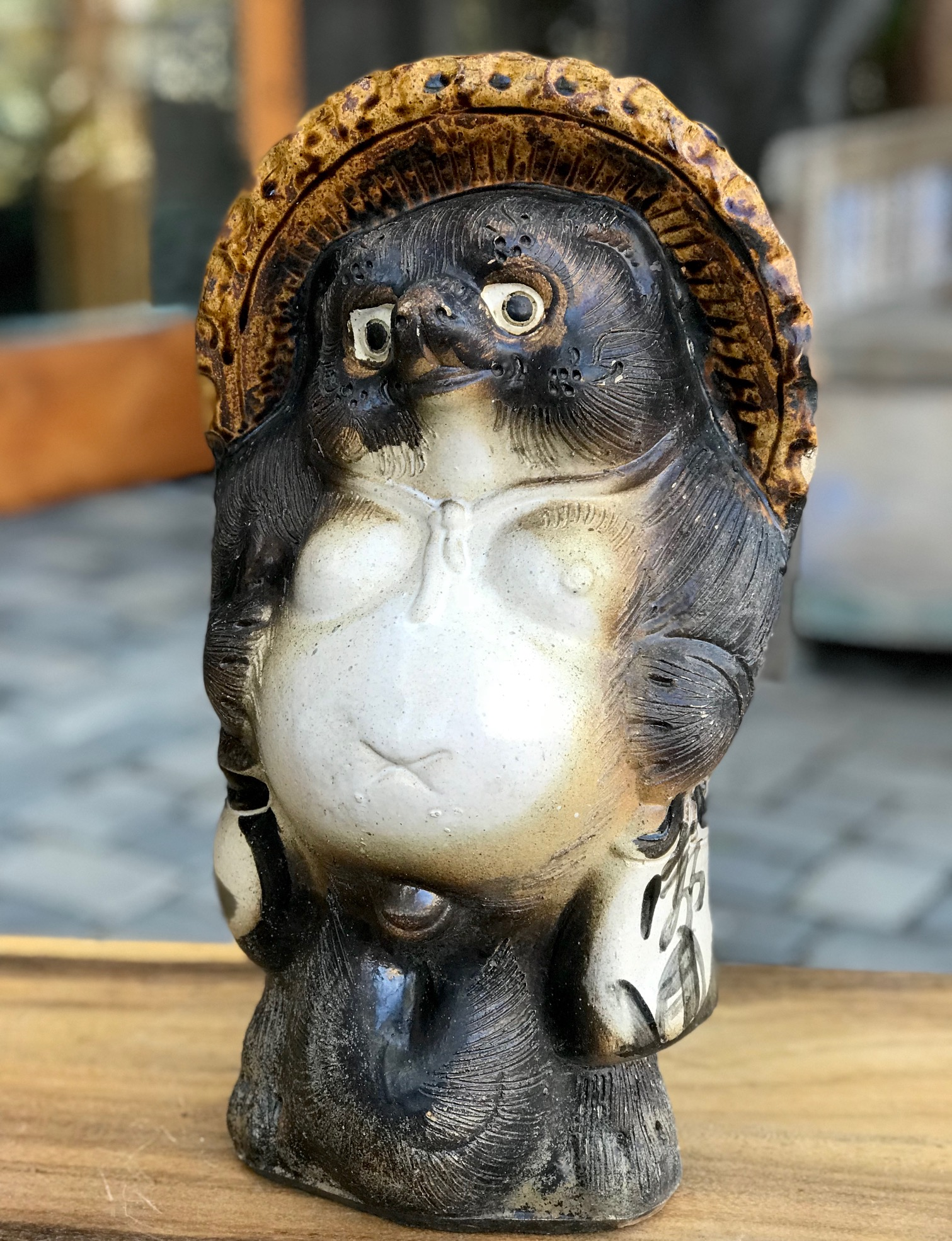 """Shigaraki Tanuki, Tanuki have a very complex and interesting folkloric history. While largely unheard of in the states, Tanuki have been among the most significant characters in Japan since ancient times. Contemporary Tanuki are primarily a welcoming symbol of prosperity. In the mid 20th century the character was adapted, both visually and symbolically, to suit modern culture and, although they retain much of their prankster persona from the original 16th century creatures, they are much more benign. They have a long list of supernatural powers, most notable shape-shifting. Ancient Tanuki, humorously portrayed in block prints are now mostly found in museums and private collections. Tanuki statues are often found in restaurant or shop windows and outside temples. Famous for getting drunk and not paying their bills, they are usually portrayed wearing a straw hat and carrying a flask of sake and a ledger of promissory notes. Thus they can also serve as cautionary figures against the hazards of overindulging in alcohol. They always have big bellies and humorously large testicles which they use as drums. 15 1/2"""" x 9"""" x 8 1/2"""", $530., thedavidalancollection.com , solana beach, ca"""