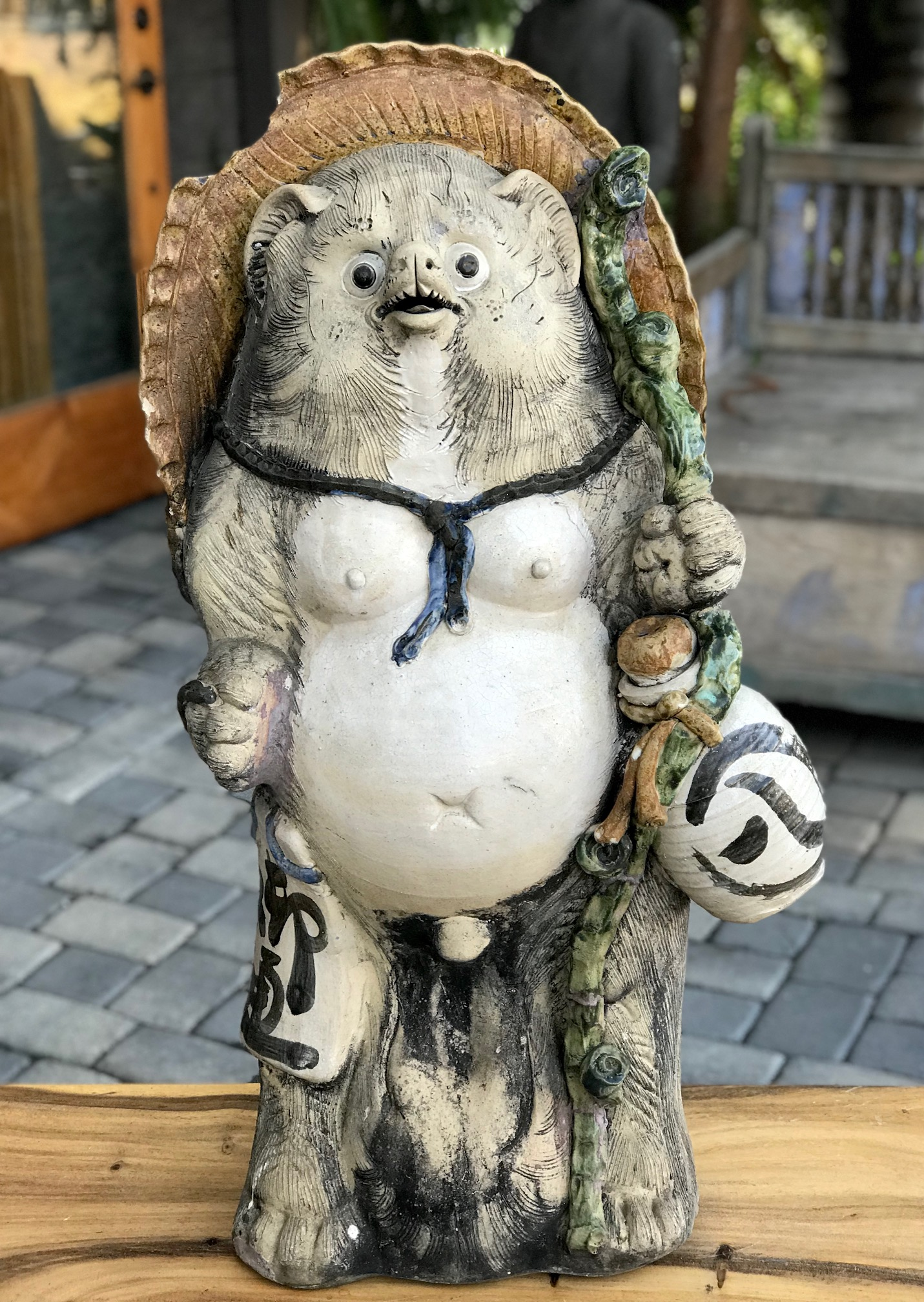 """Shigaraki Tanuki, Tanuki have a very complex and interesting folkloric history. While largely unheard of in the states, Tanuki have been among the most significant characters in Japan since ancient times. Contemporary Tanuki are primarily a welcoming symbol of prosperity. In the mid 20th century the character was adapted, both visually and symbolically, to suit modern culture and, although they retain much of their prankster persona from the original 16th century creatures, they are much more benign. They have a long list of supernatural powers, most notable shape-shifting. Ancient Tanuki, humorously portrayed in block prints are now mostly found in museums and private collections. Tanuki statues are often found in restaurant or shop windows and outside temples. Famous for getting drunk and not paying their bills, they are usually portrayed wearing a straw hat and carrying a flask of sake and a ledger of promissory notes. Thus they can also serve as cautionary figures against the hazards of overindulging in alcohol. They always have big bellies and humorously large testicles which they use as drums. 37"""" x 19"""" x 16"""", $950., (chip in hat) thedavidalancollection.com , solana beach, ca"""