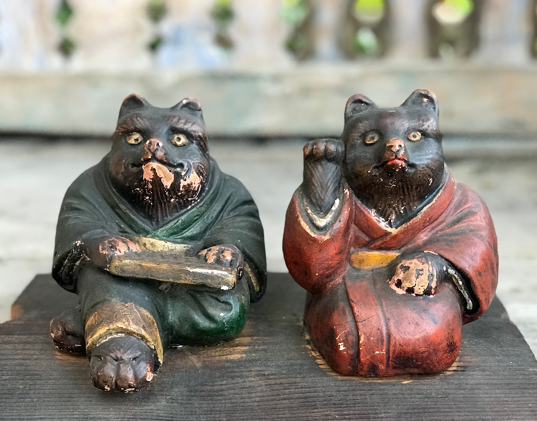 """2 Wooden Tanuki in kimonos with abacus, and calling for good luck, Tanuki have a very complex and interesting folkloric history. While largely unheard of in the states, Tanuki have been among the most significant characters in Japan since ancient times. Contemporary Tanuki are primarily a welcoming symbol of prosperity. In the mid 20th century the character was adapted, both visually and symbolically, to suit modern culture and, although they retain much of their prankster persona from the original 16th century creatures, they are much more benign. They have a long list of supernatural powers, most notable shape-shifting. Ancient Tanuki, humorously portrayed in block prints are now mostly found in museums and private collections. Tanuki statues are often found in restaurant or shop windows and outside temples. Famous for getting drunk and not paying their bills, they are usually portrayed wearing a straw hat and carrying a flask of sake and a ledger of promissory notes. Thus they can also serve as cautionary figures against the hazards of overindulging in alcohol. They always have big bellies and humorously large testicles which they use as drums. 5"""" x 10 1/4"""" x 7 1/2"""", sold., thedavidalancollection.com , solana beach, ca"""