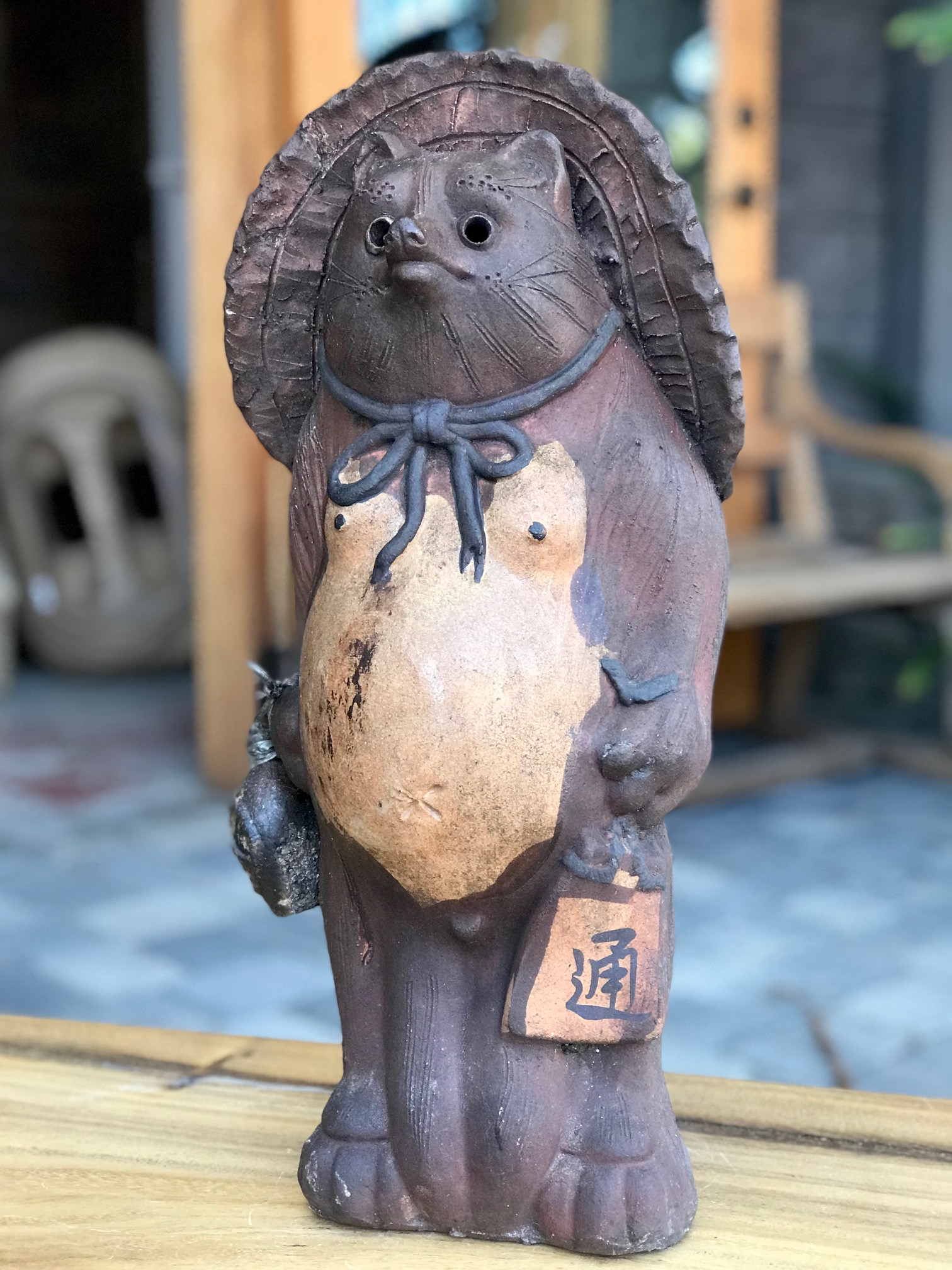 """Shigaraki Tanuki, (unglazed) Tanuki have a very complex and interesting folkloric history. While largely unheard of in the states, Tanuki have been among the most significant characters in Japan since ancient times. Contemporary Tanuki are primarily a welcoming symbol of prosperity. In the mid 20th century the character was adapted, both visually and symbolically, to suit modern culture and, although they retain much of their prankster persona from the original 16th century creatures, they are much more benign. They have a long list of supernatural powers, most notable shape-shifting. Ancient Tanuki, humorously portrayed in block prints are now mostly found in museums and private collections. Tanuki statues are often found in restaurant or shop windows and outside temples. Famous for getting drunk and not paying their bills, they are usually portrayed wearing a straw hat and carrying a flask of sake and a ledger of promissory notes. Thus they can also serve as cautionary figures against the hazards of overindulging in alcohol. They always have big bellies and humorously large testicles which they use as drums. 18"""" x 8 1/2"""" x 7 b1/2"""", $540., thedavidalancollection.com , solana beach, ca"""