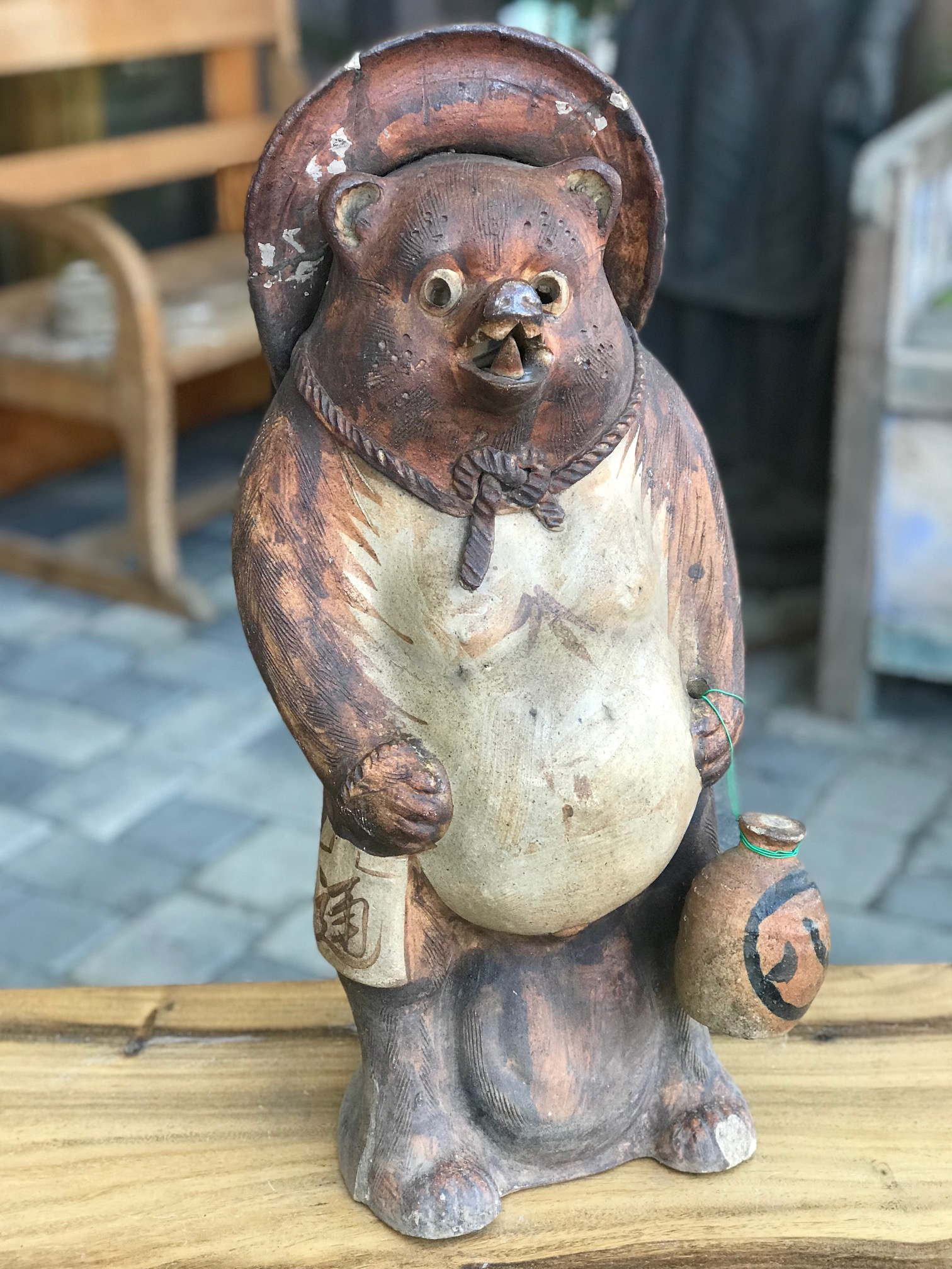 """Shigaraki Tanuki, (unglazed) Tanuki have a very complex and interesting folkloric history. While largely unheard of in the states, Tanuki have been among the most significant characters in Japan since ancient times. Contemporary Tanuki are primarily a welcoming symbol of prosperity. In the mid 20th century the character was adapted, both visually and symbolically, to suit modern culture and, although they retain much of their prankster persona from the original 16th century creatures, they are much more benign. They have a long list of supernatural powers, most notable shape-shifting. Ancient Tanuki, humorously portrayed in block prints are now mostly found in museums and private collections. Tanuki statues are often found in restaurant or shop windows and outside temples. Famous for getting drunk and not paying their bills, they are usually portrayed wearing a straw hat and carrying a flask of sake and a ledger of promissory notes. Thus they can also serve as cautionary figures against the hazards of overindulging in alcohol. They always have big bellies and humorously large testicles which they use as drums. 23 1/2"""" x 11 1/2"""" x 11"""", $675., thedavidalancollection.com , solana beach, ca"""