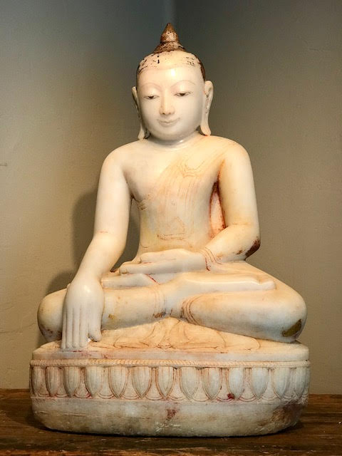 """Marble Buddha, Shan Style, 17th century. Hand carved with a smooth finish and painted with gold gilt and red pigment. Museum quality condition, wear is consistent with age. Buddha is sitting in the lotus position (legs crossed with soles of feet up) with hands in 'Bhumisparsha mudra' position - calling the earth to witness his enlightenment. Seated on a Lotus design base. His serene demeanor and monastic robes show great carving skill and artistry. Dimensions: 32"""" tall x 21.5 wide x 13.5 deep. $34,000."""