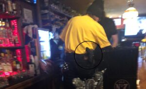 West Virginia bartender pouring beer, wearing open-carry sidearm