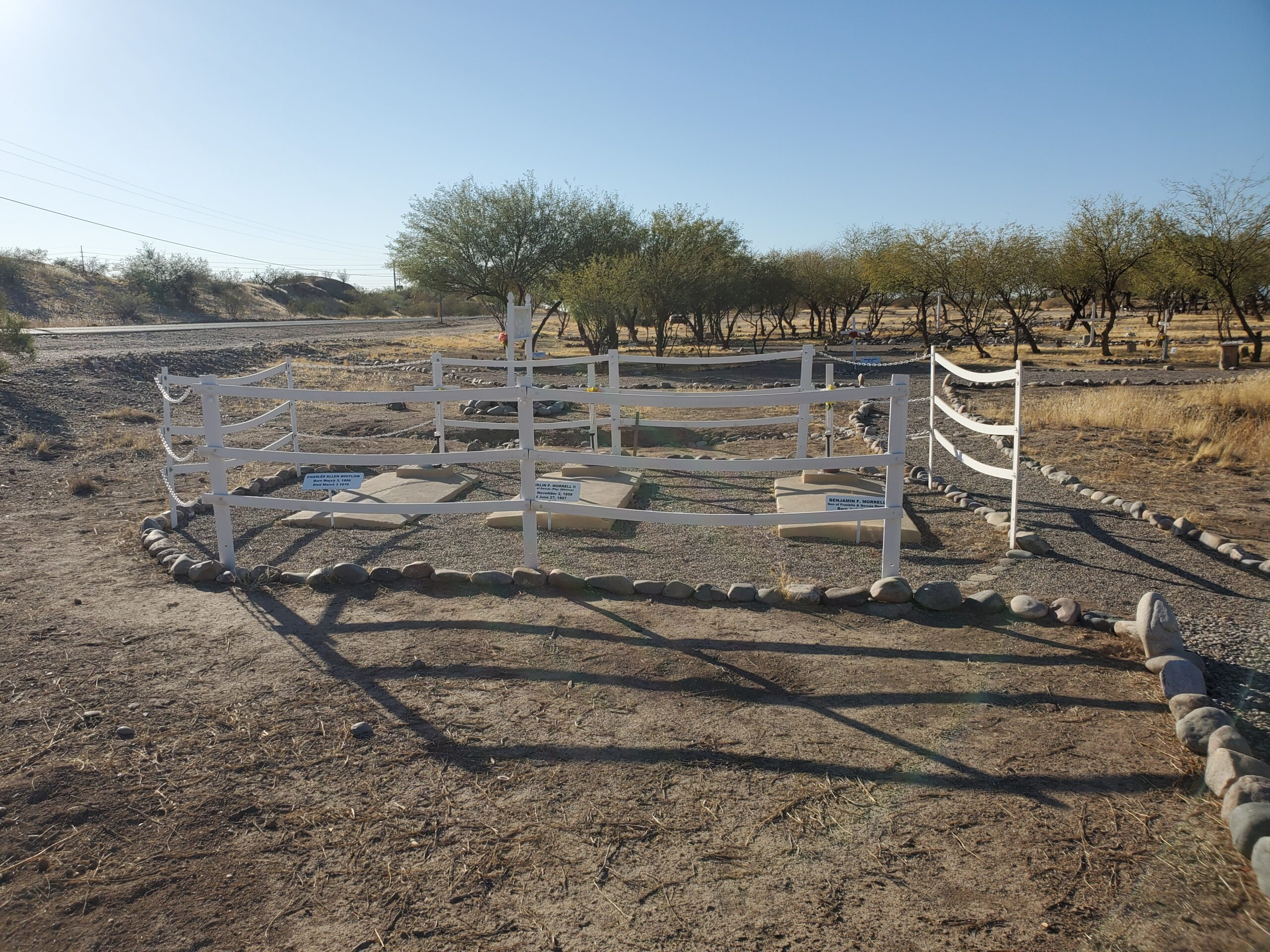 Three graves marked with concrete slabs surrounded by a white fence